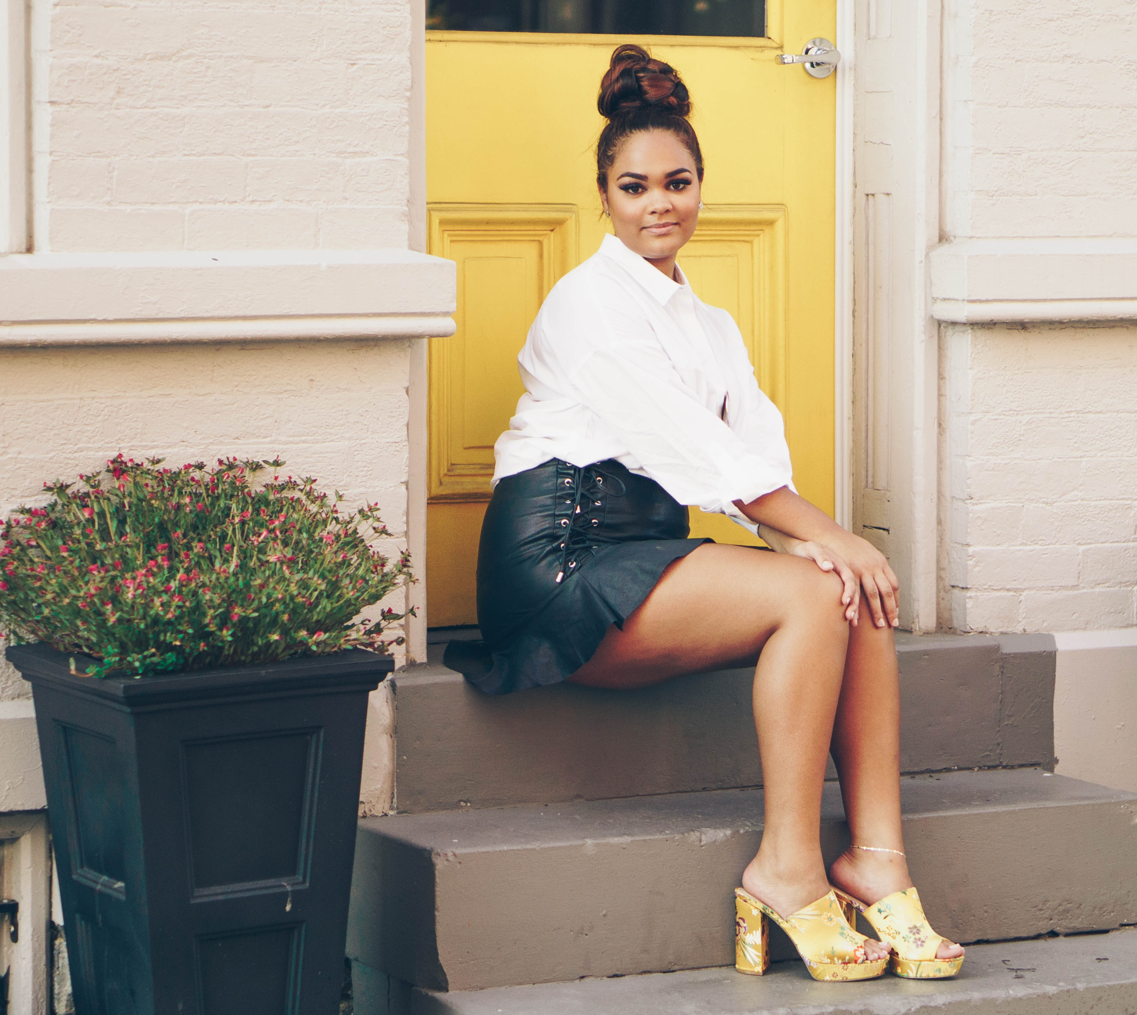 girl wearing a white shirt and black laced skirt sat on steps in front of a yellow door