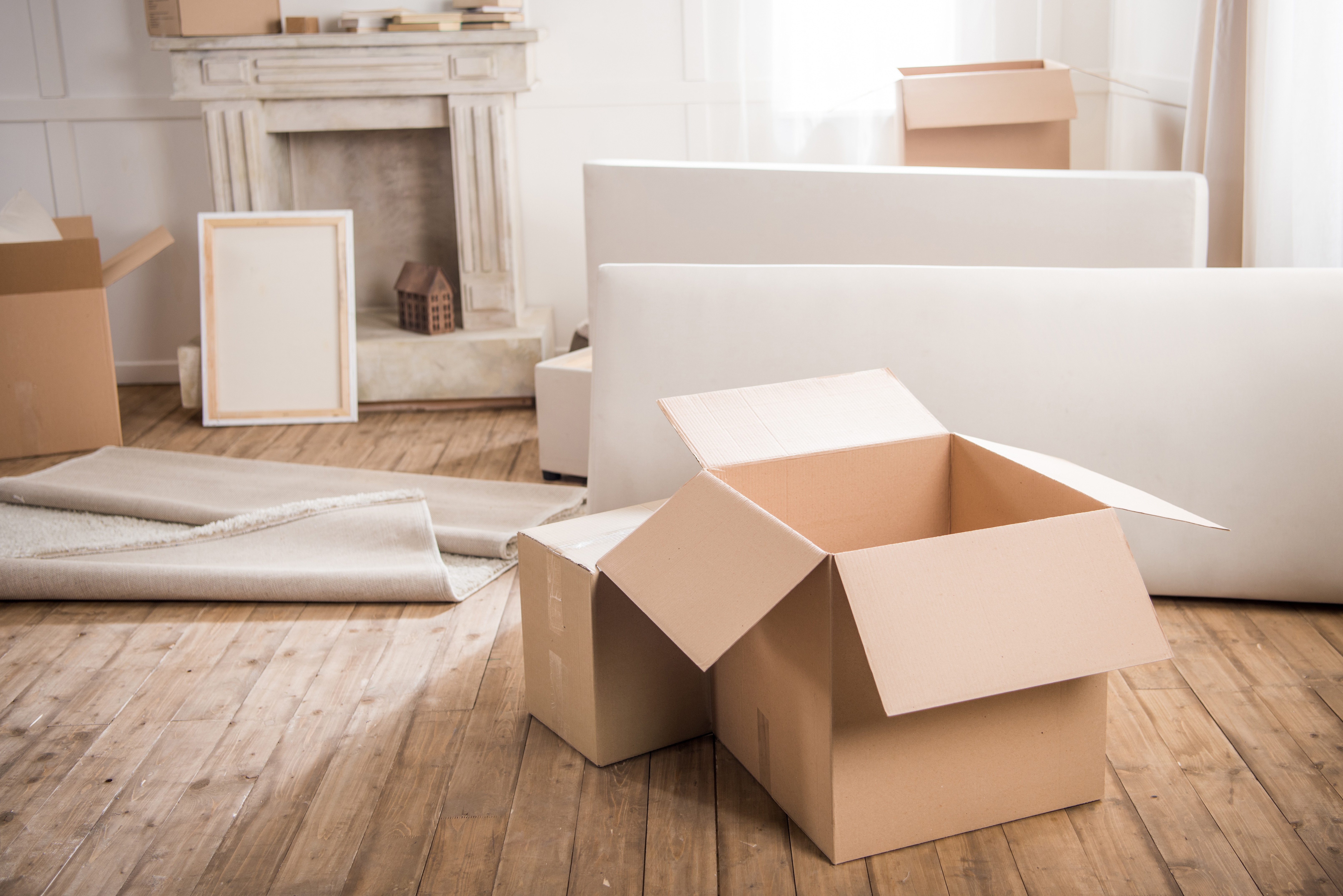 cardboard boxes in a half empty room with cloth on a wooden floor and packing materials