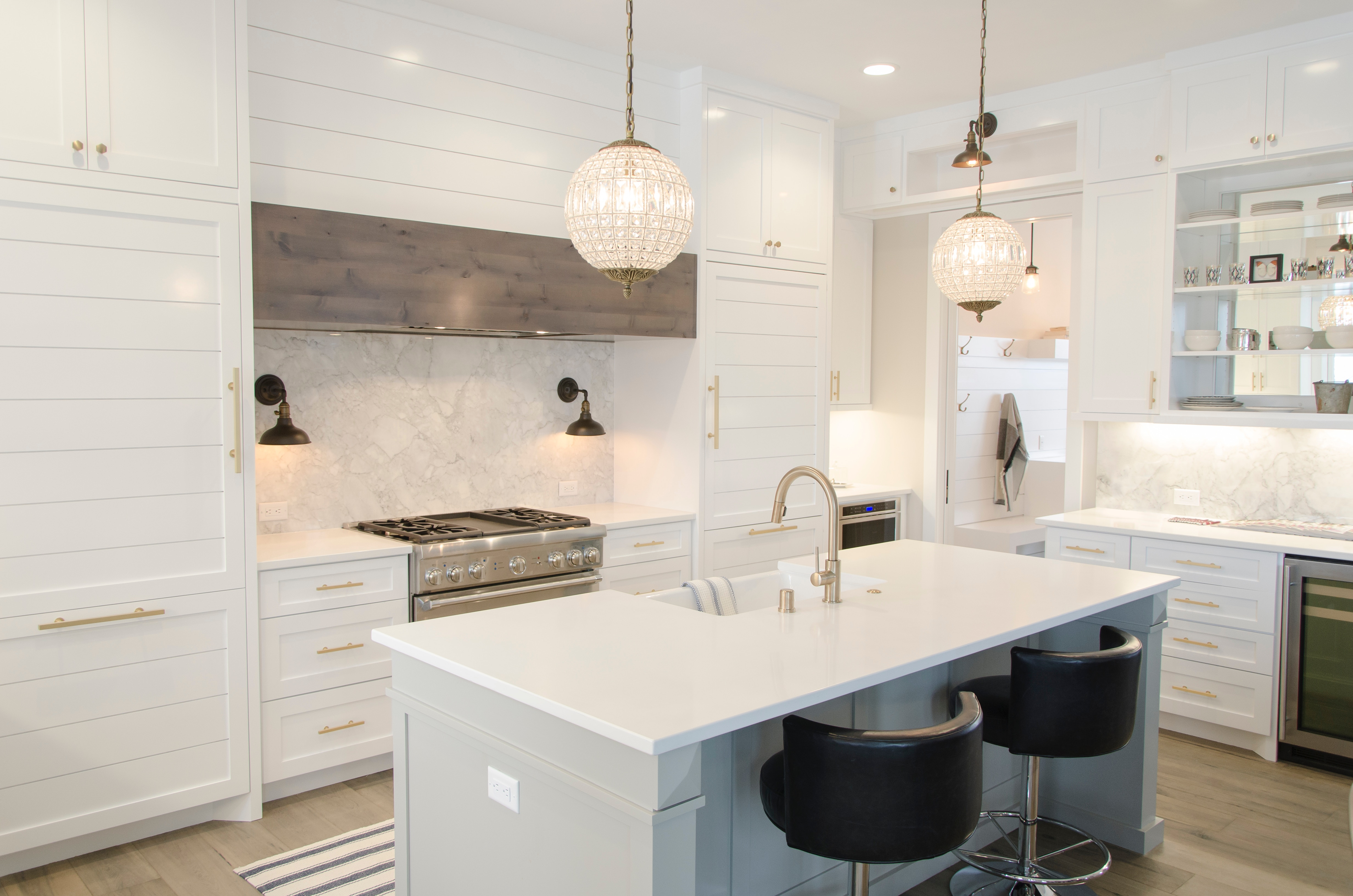 a white high gloss designed kitchen with an island in the middle and modern features and lighting