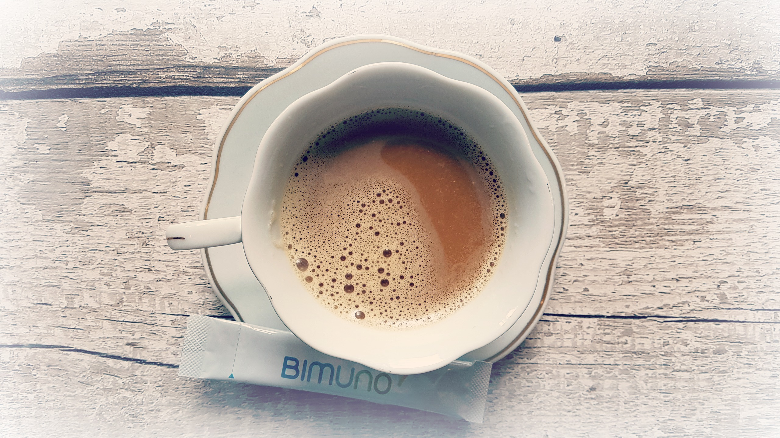 a sachet of bimuno daily on the saucer of a teacup with coffee in the cup