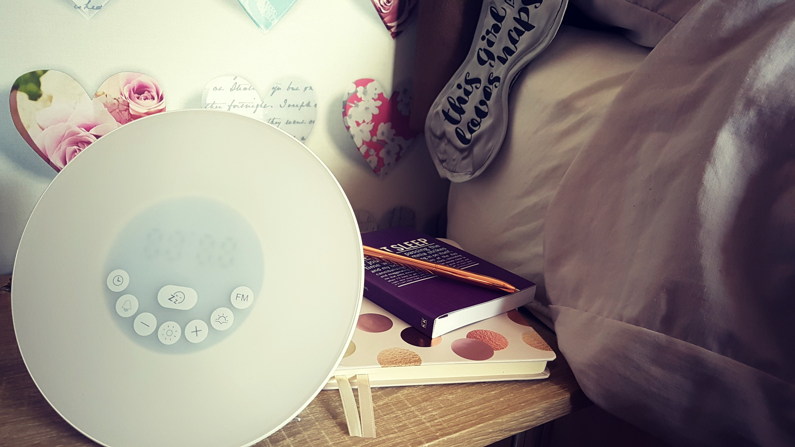 a lifebee wake up light on a bedside table with journals and pends and an eye mask on the side of the bed