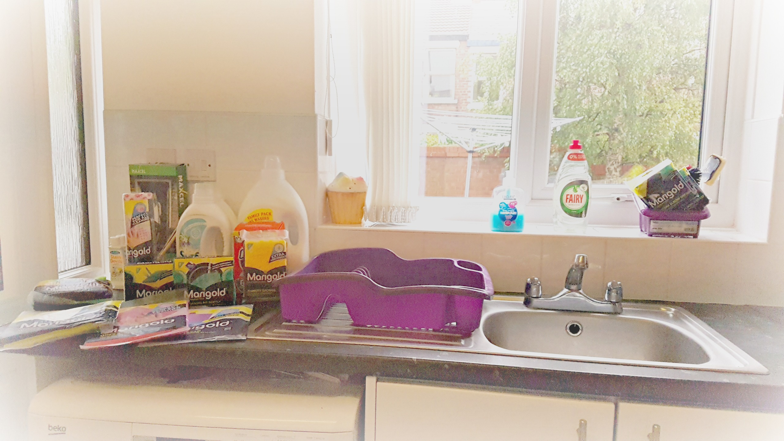 a kitchen sink in fornt of a windwo with marigold cleaning products to the left