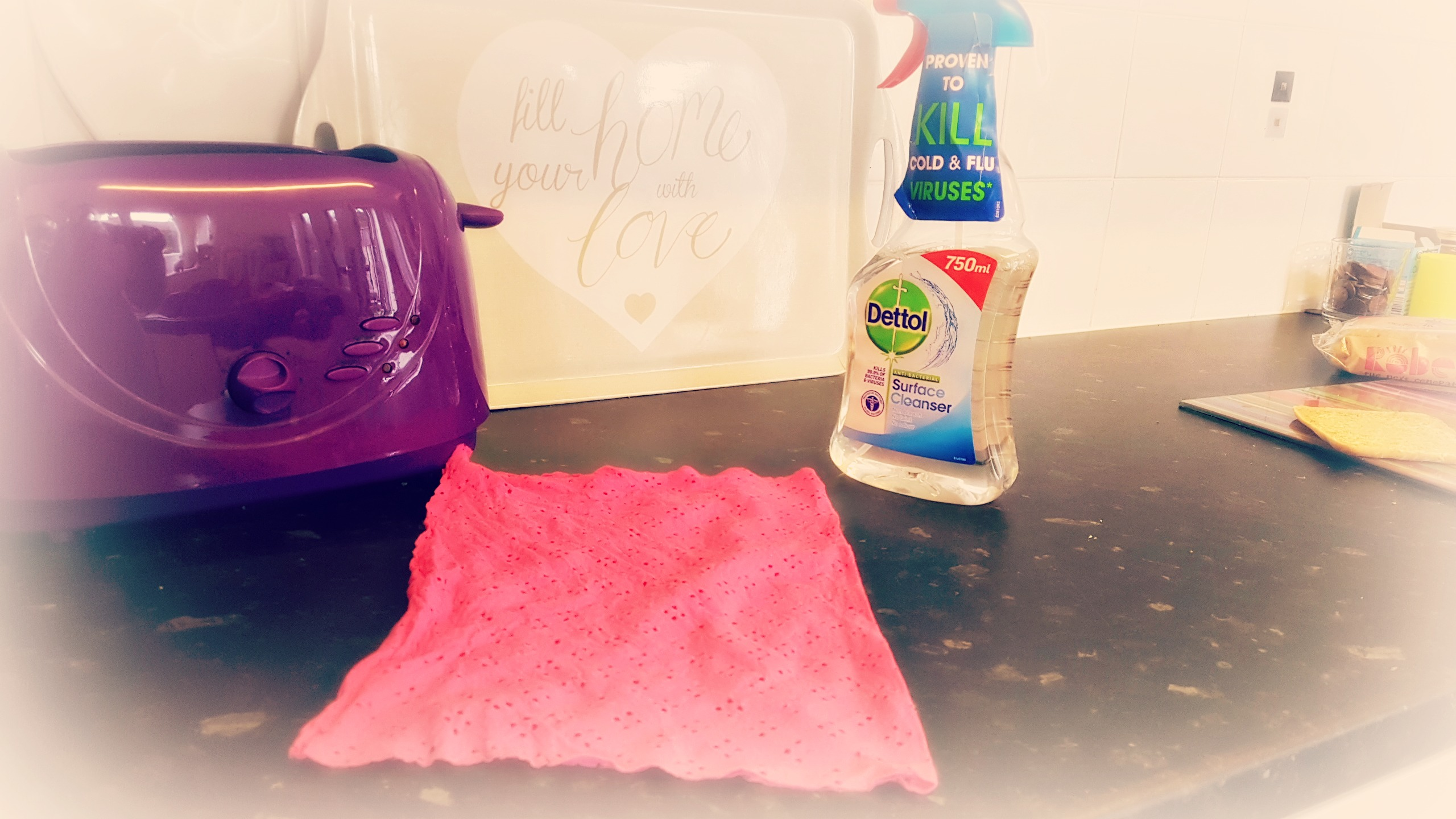 a kitchen sideboard with a purple toaster pink marigold cleaning cloth and bottle of dettol spray