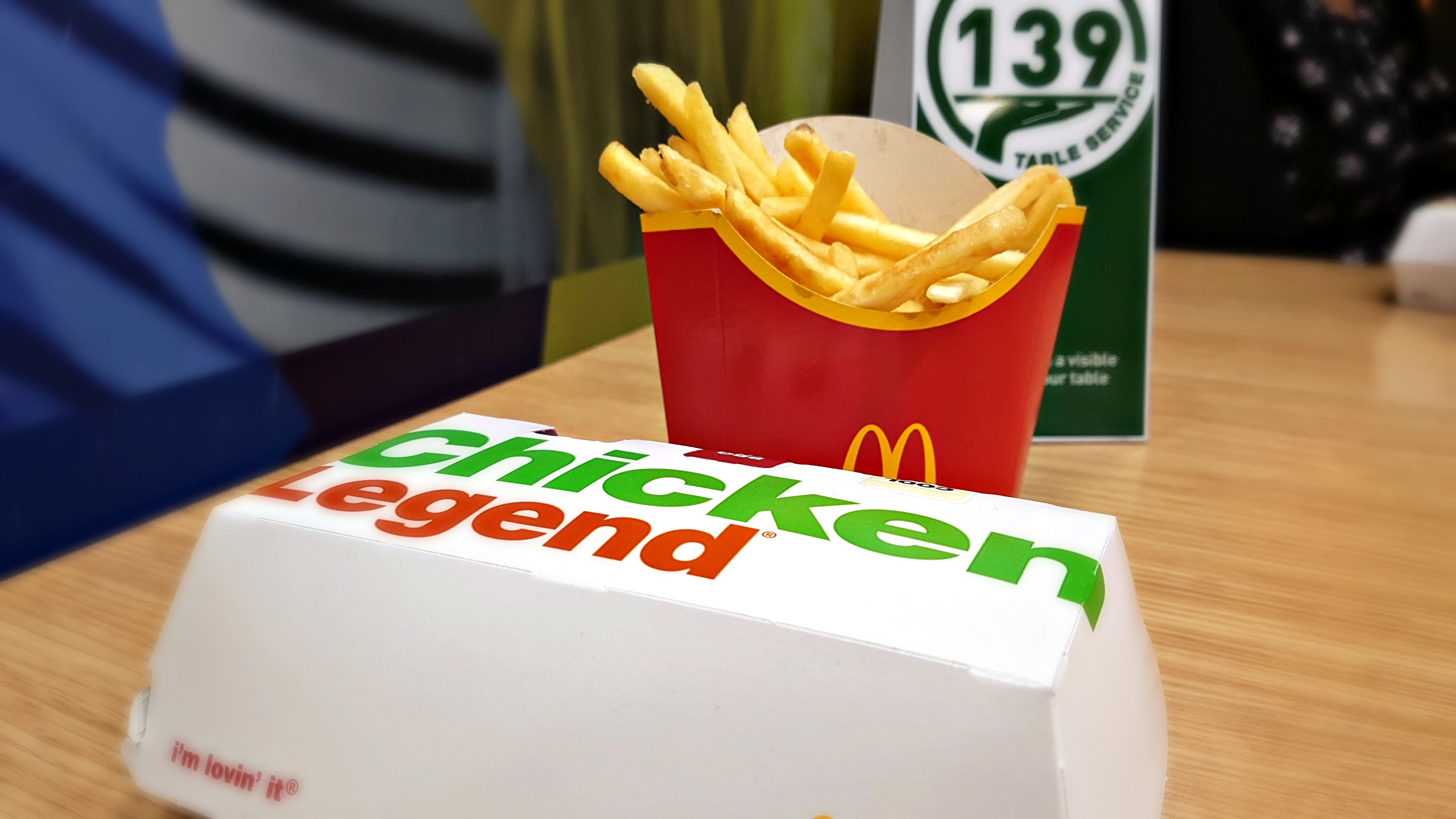 image of a mcdonald's click and collect app order of fries and a closed boxed chicken legend with a table number in the background