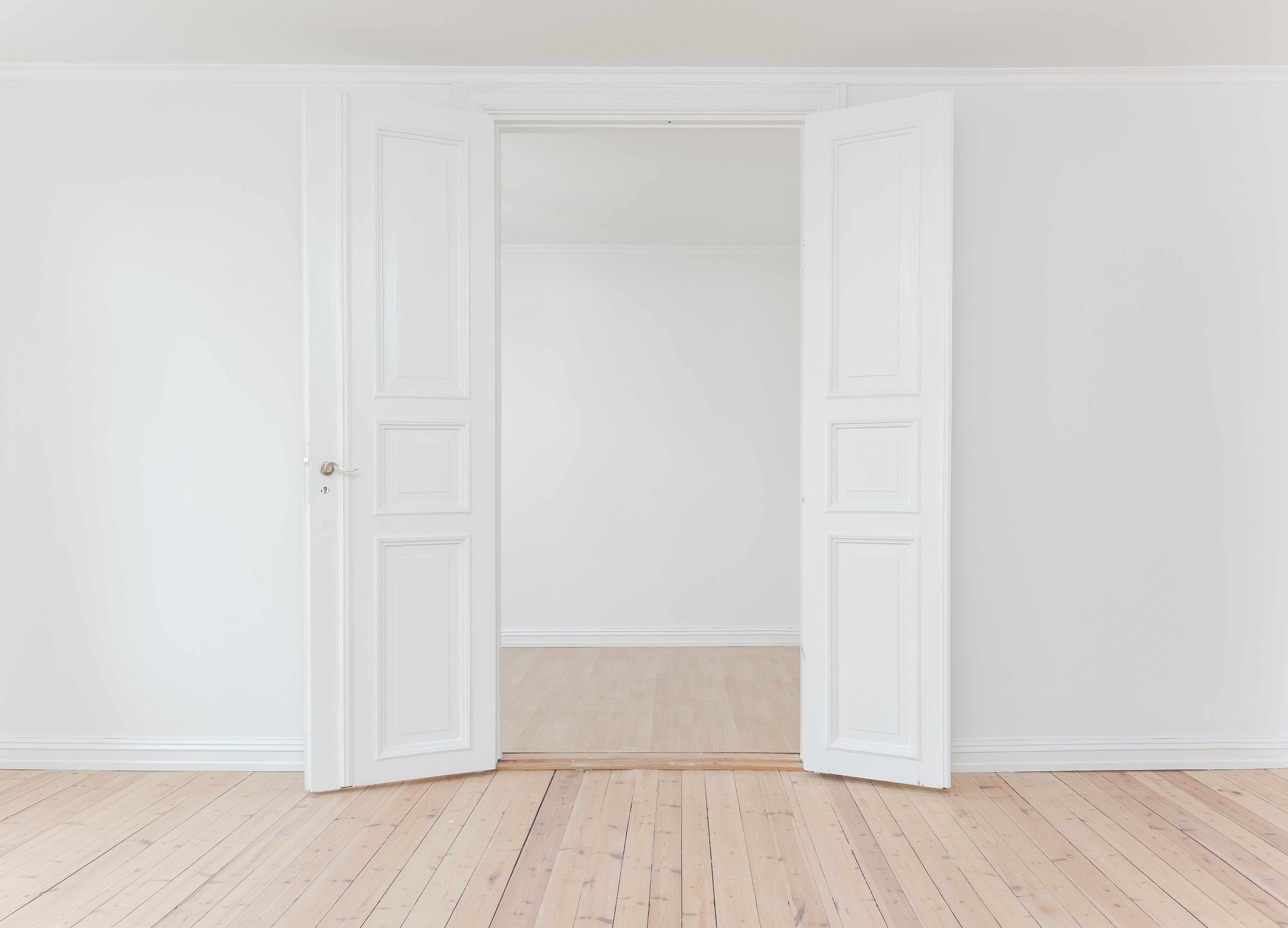 an empty room with wooden flooring and white walls with a white double door open leading to another room