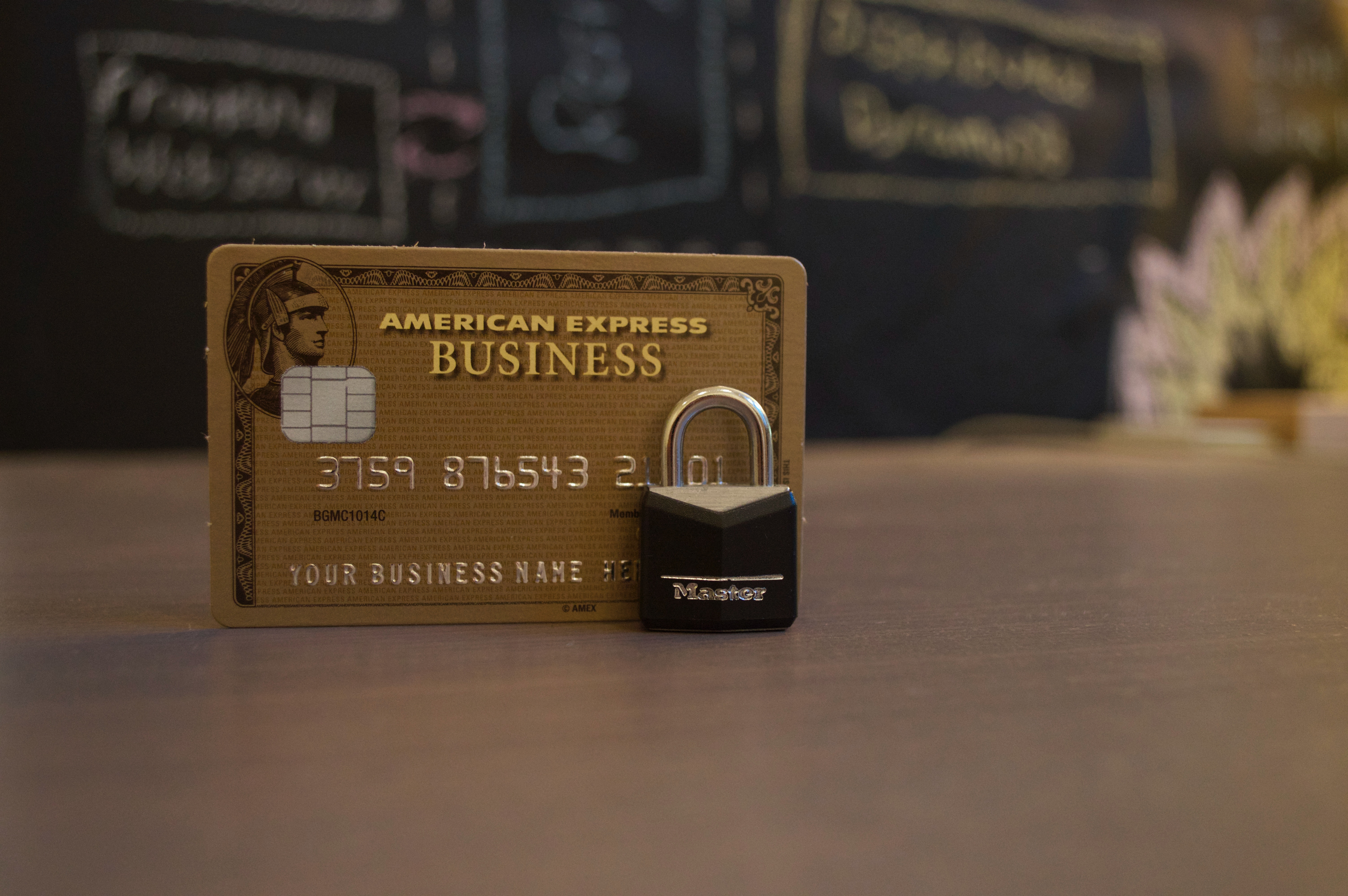 brown american express card on a desk next to a padlock