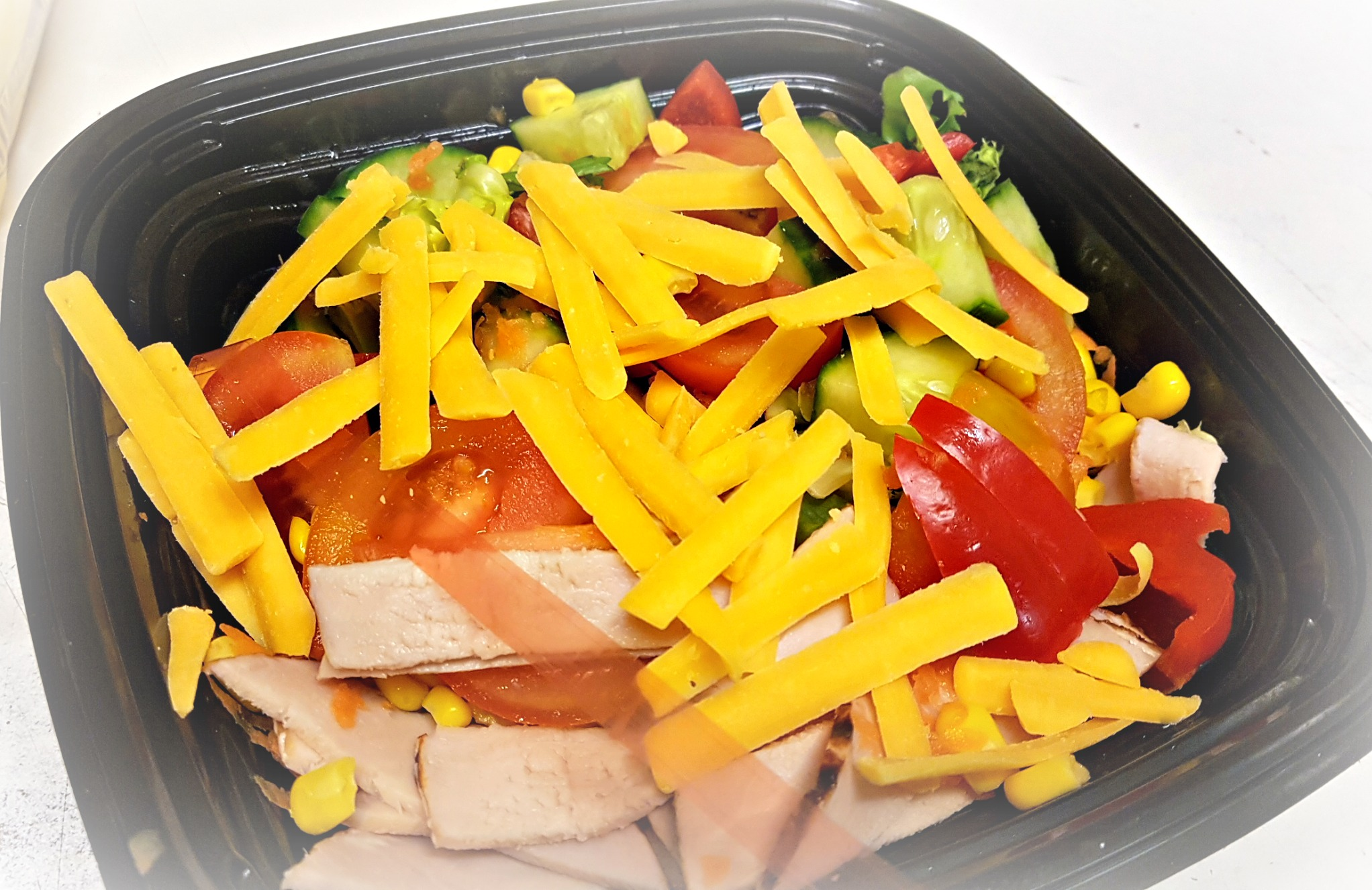 mixed salad in a black dish with cheese sprinkled on top