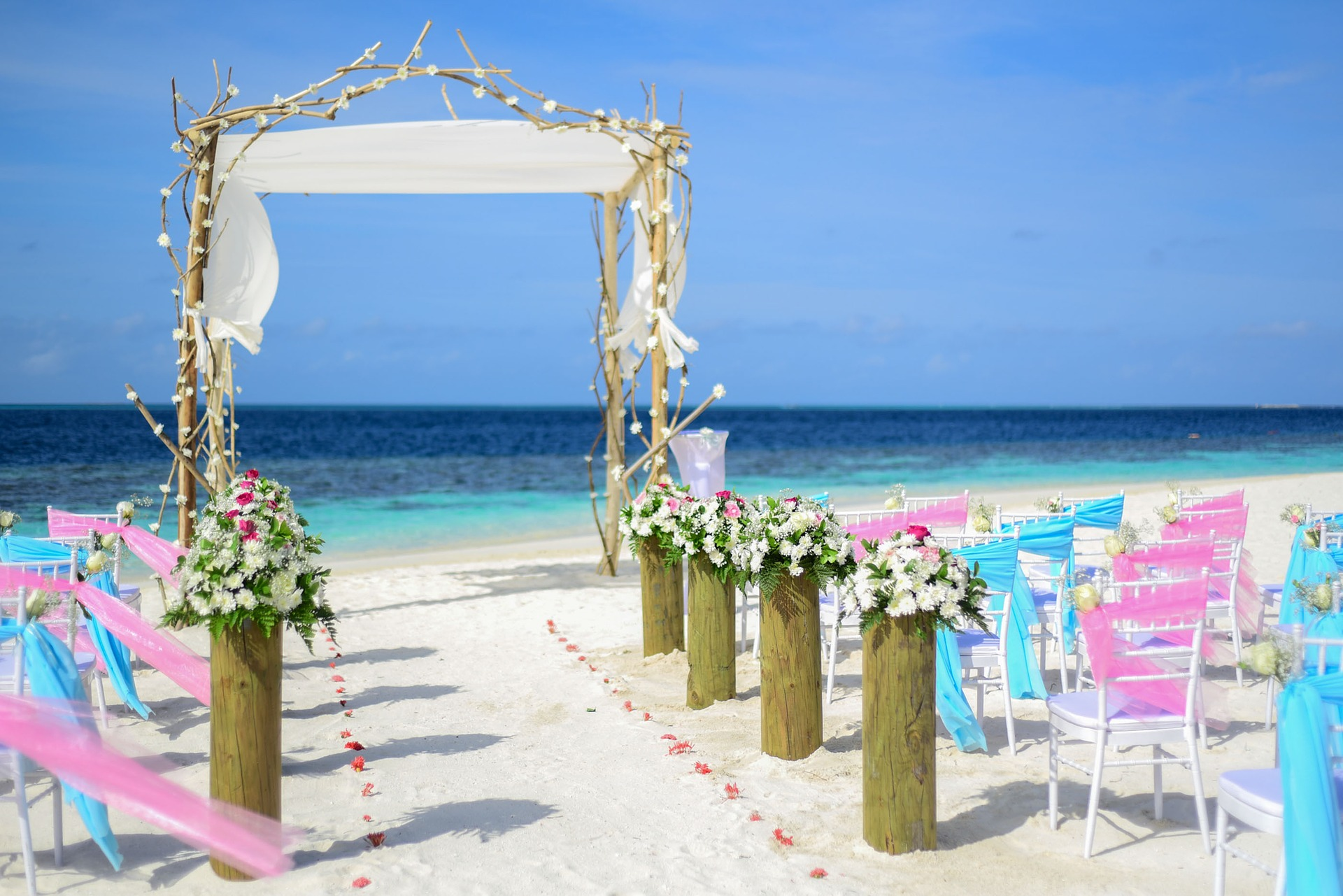 destination wedding on the beach with white chairs with pink and blue ribbons on and a wooden arch decorated with flowers