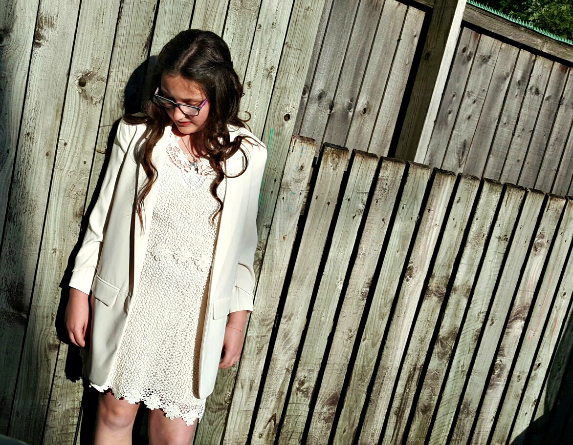 girl in white dress with crochet flowers and whit blazer looking at the floor standing in front of a tall wooden fence