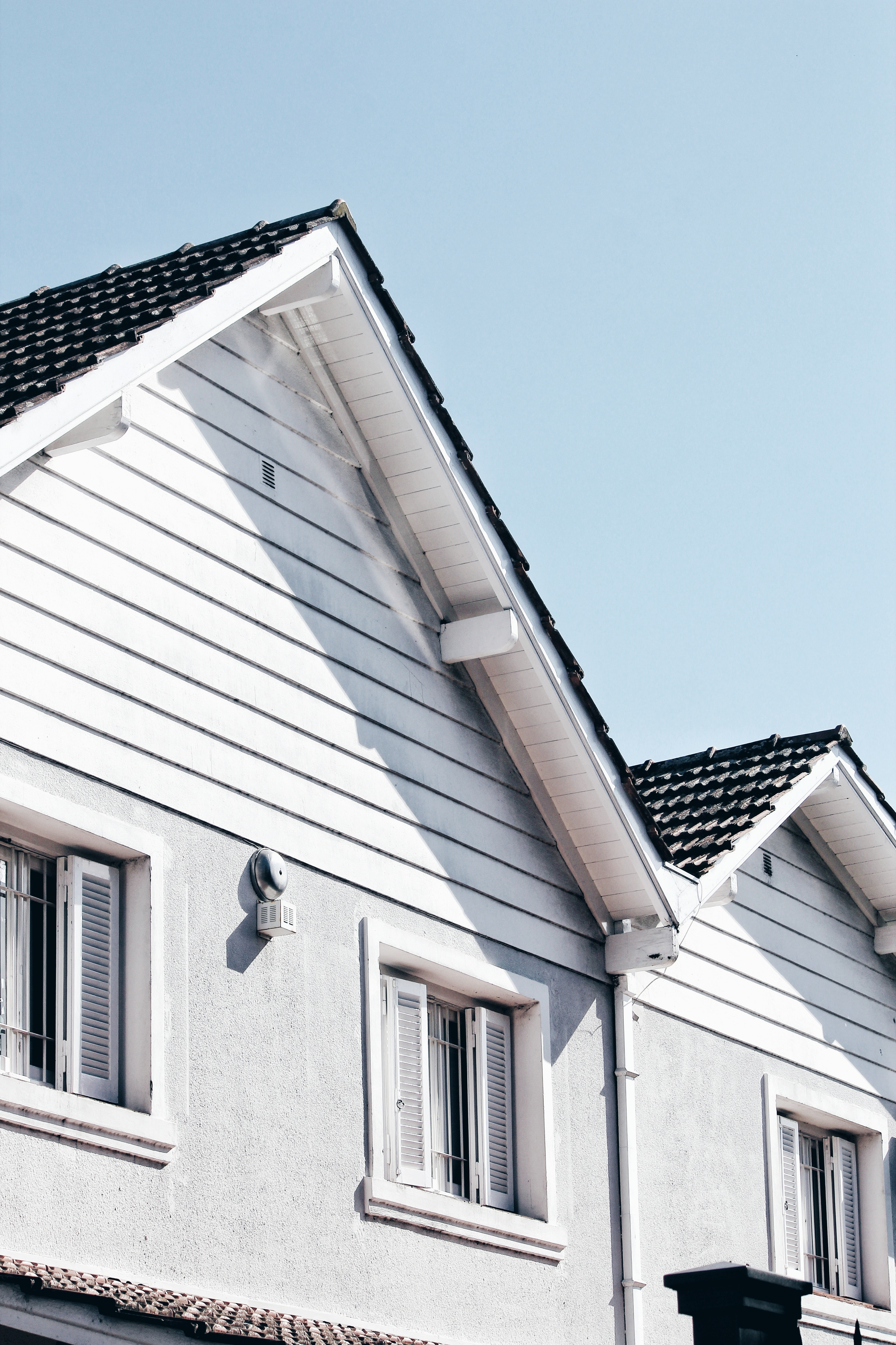 pointed roof of a house with white woodwork and white window shutters