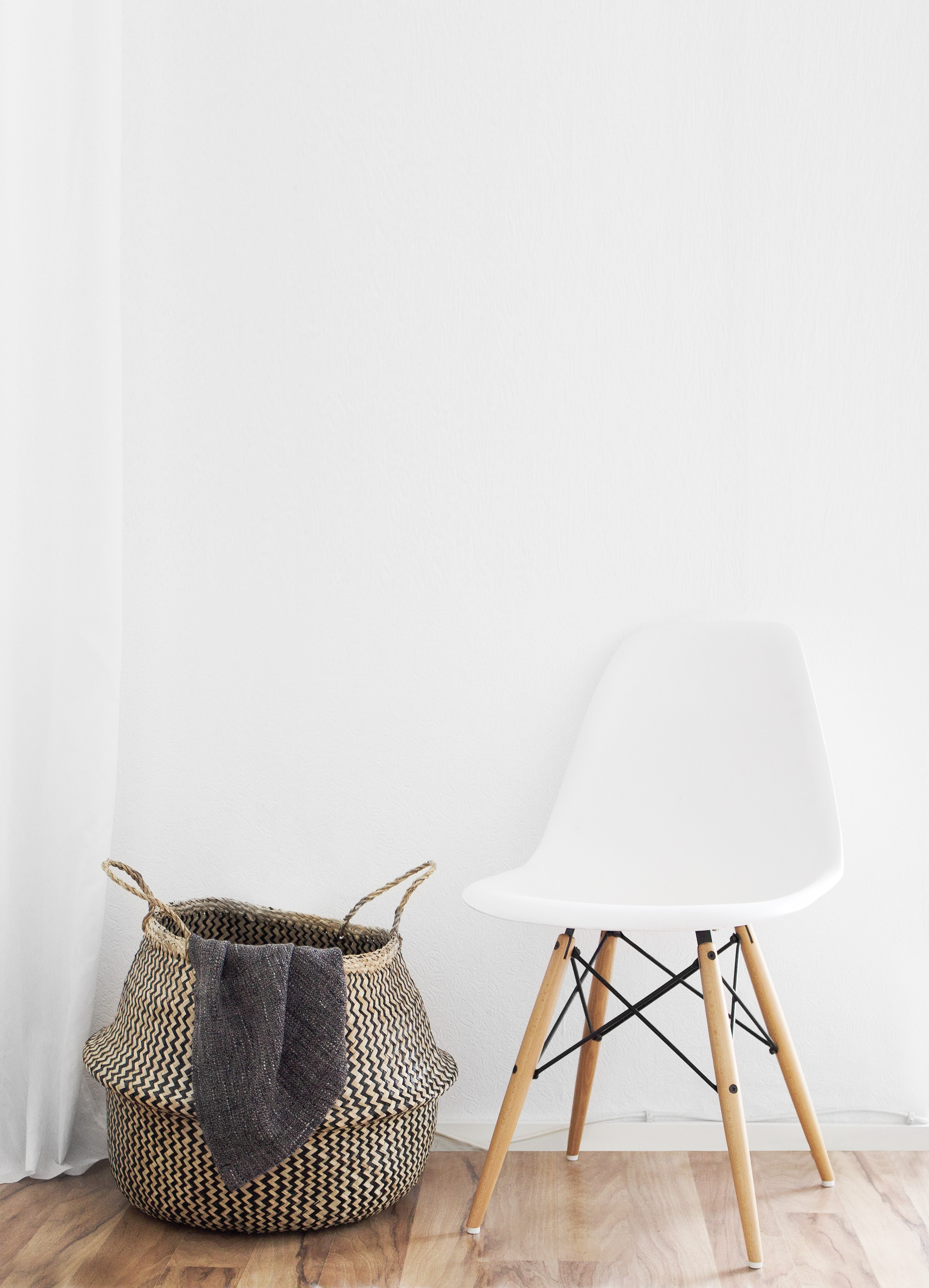 white eames chair with a laundry basket next to it