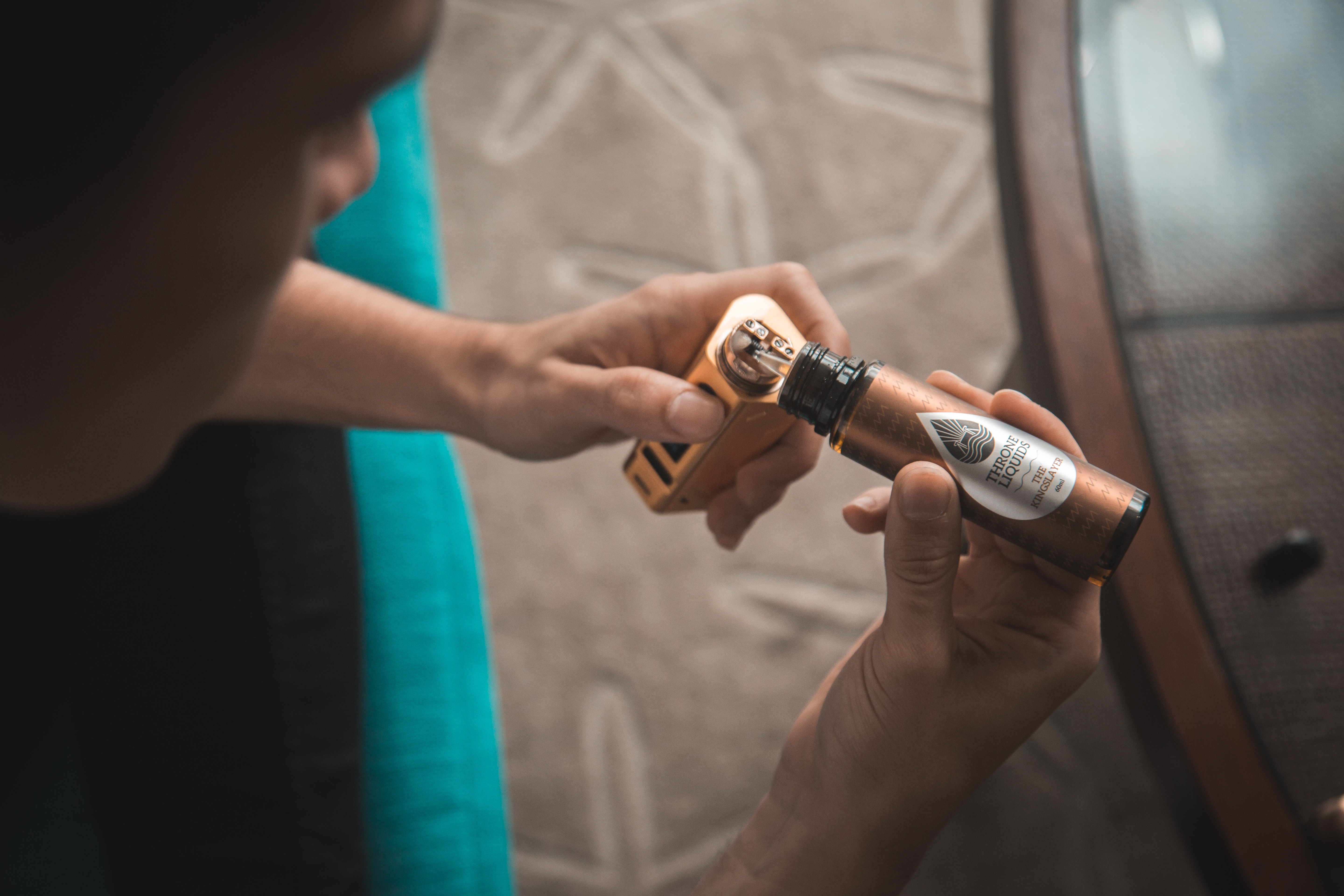 persons hand filling a vape