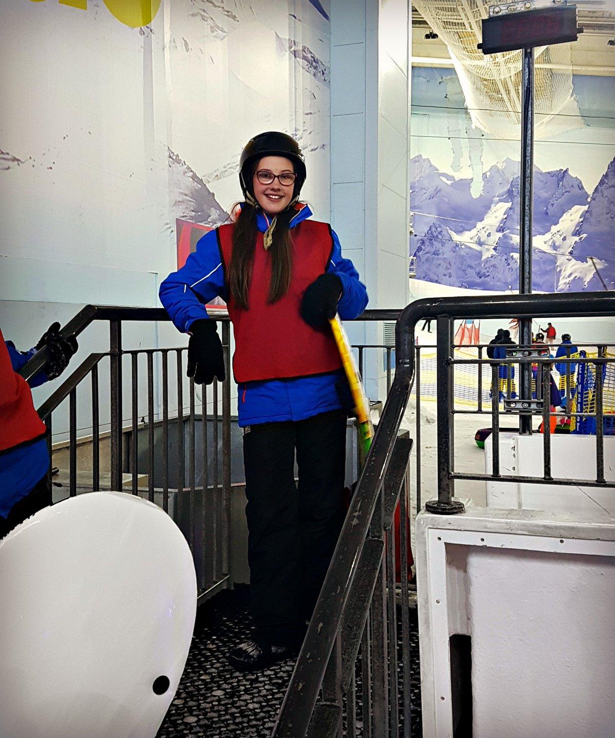girl in ski clothing standing on steps