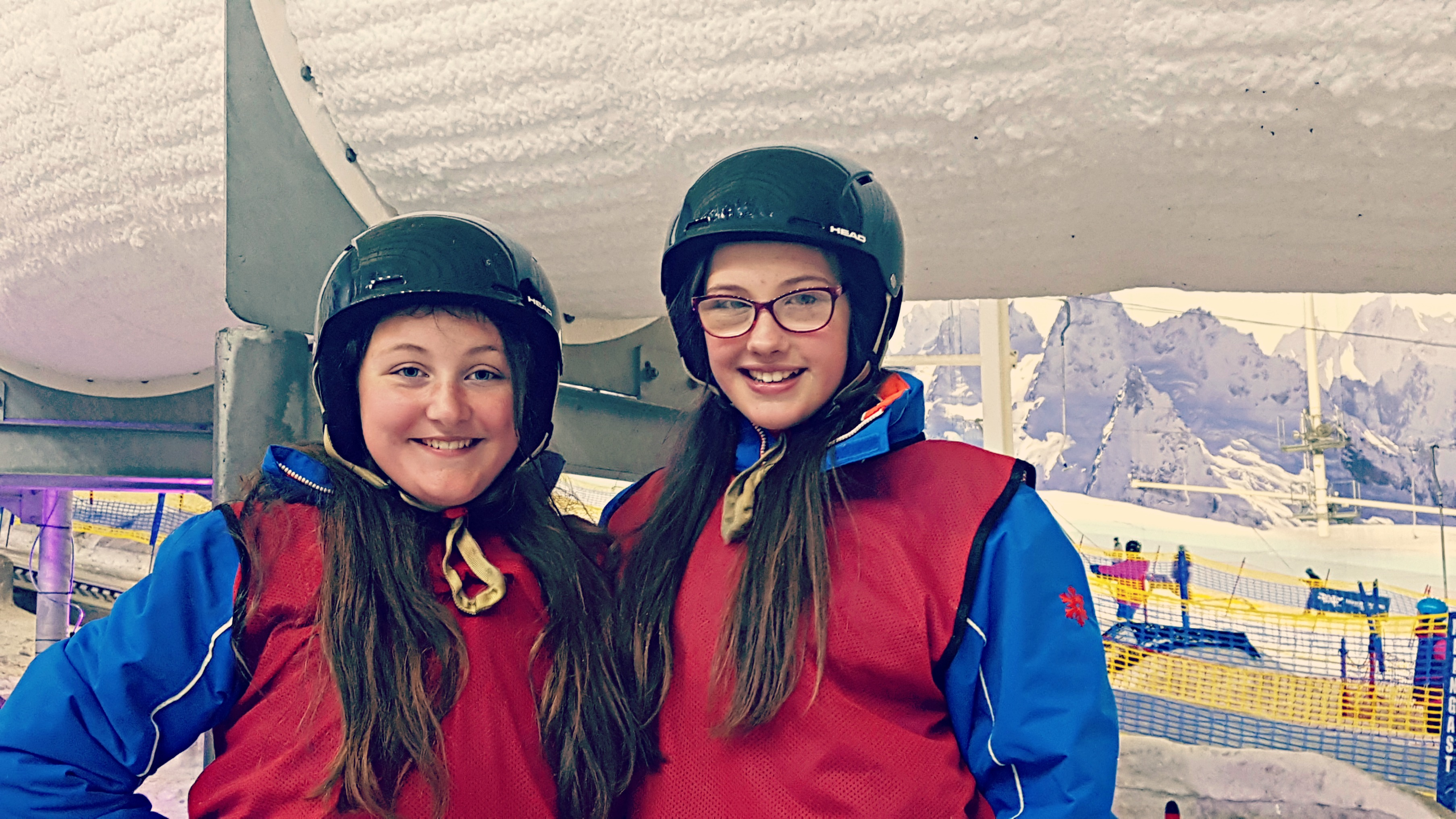 2 girls in helmets and ski wear a an indoor ski park