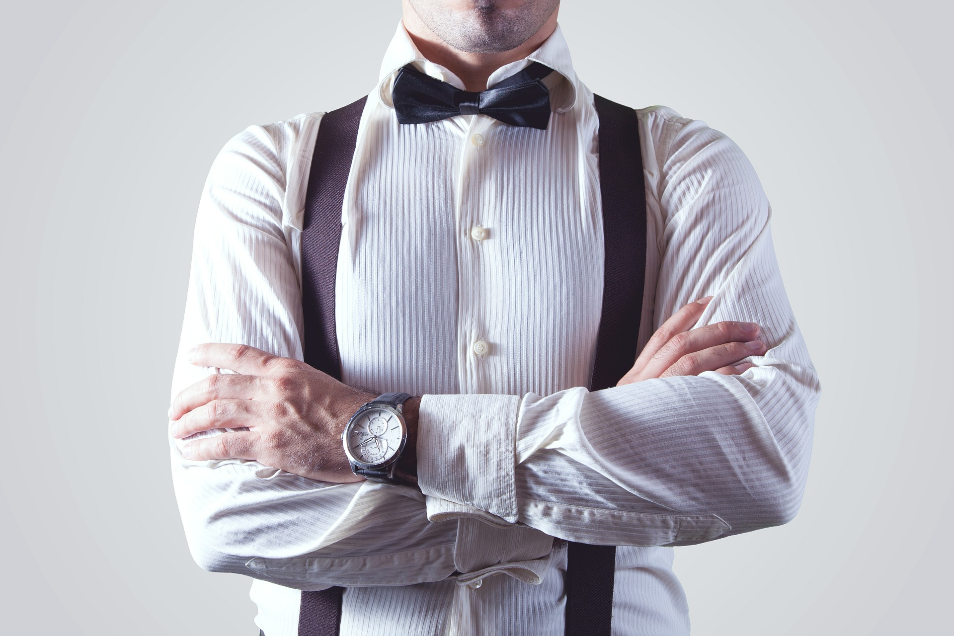 man wearing white ribbed shirt with braces and bow tie with a wristwatch