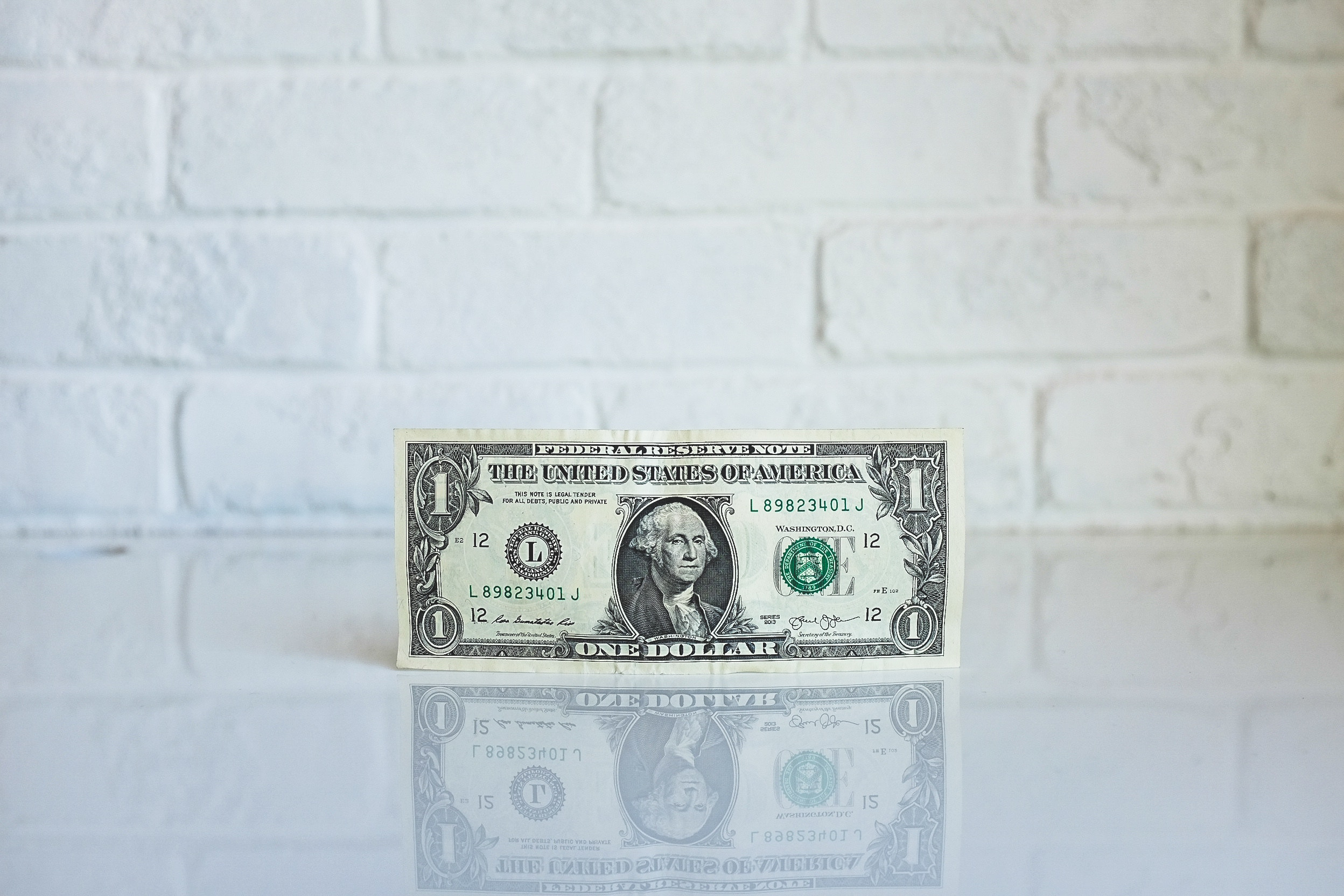 image of a one dollar bill on a white glossy surface in front of a white brick wall
