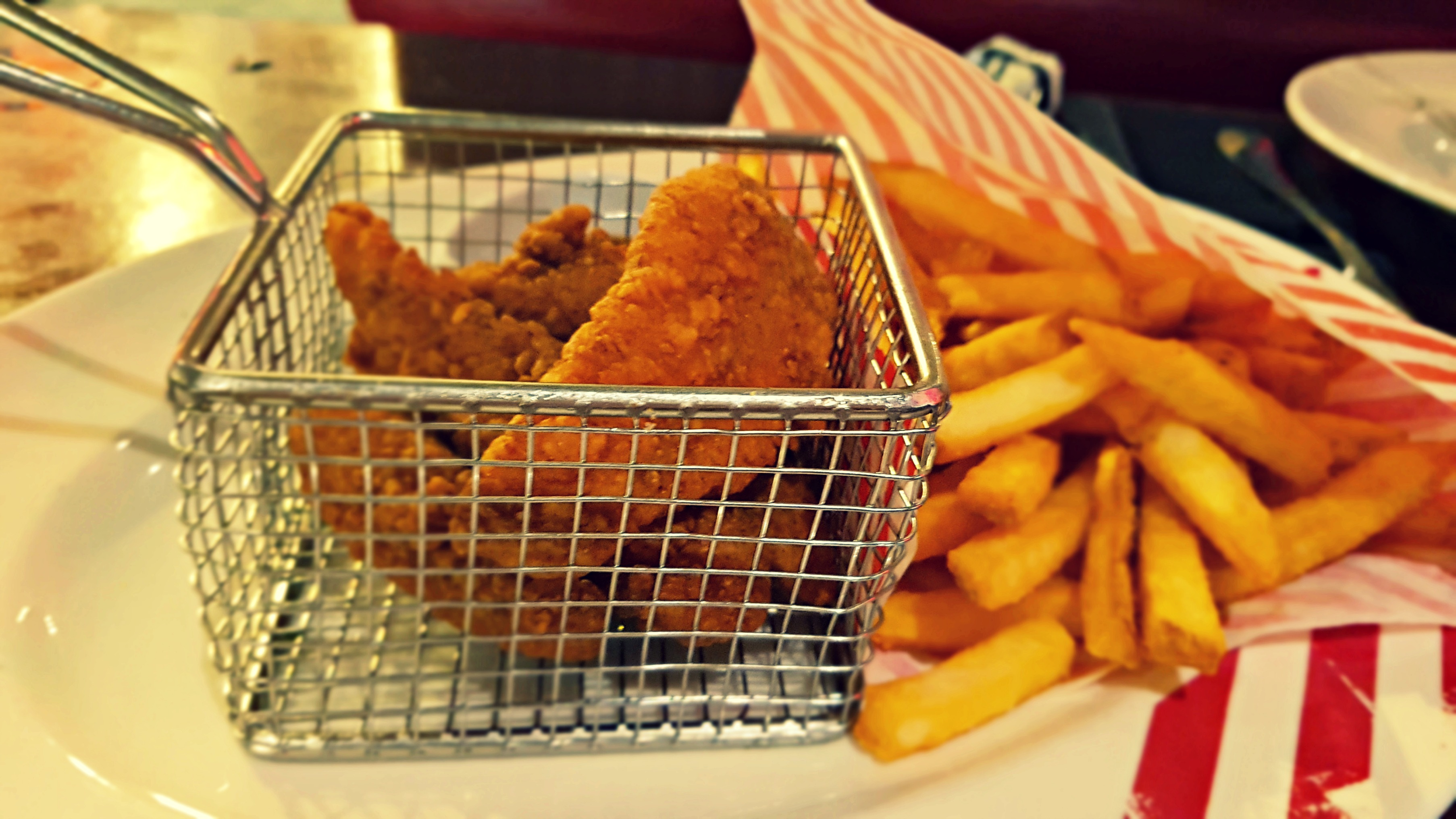 chicken fingers in a little metal serving basket with fries from tgi fridays