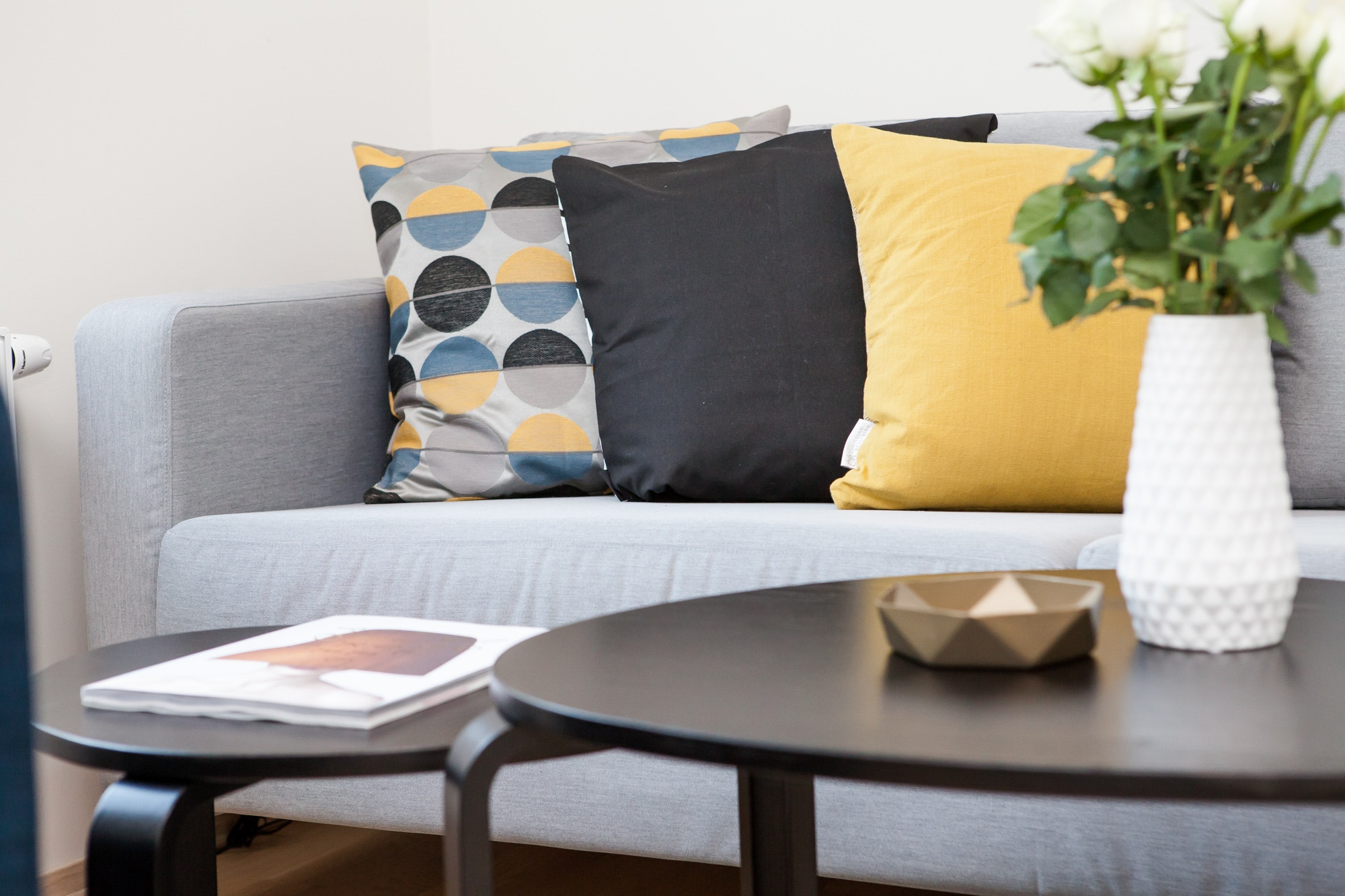 grey sofa with yellow scatter cushions behind a black coffee table with a vase with flowers  in