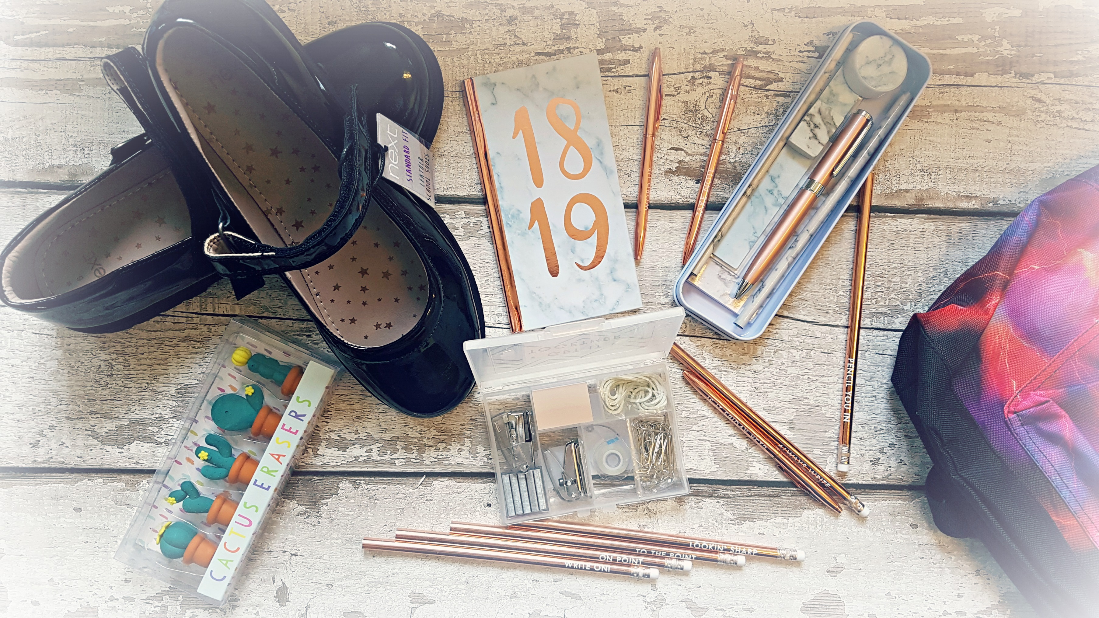 a flatlay of stationery items includng pens and pencils in rose gold with quotes on them, 18/19 school diary, black mary jane school shoes and a pink school bag