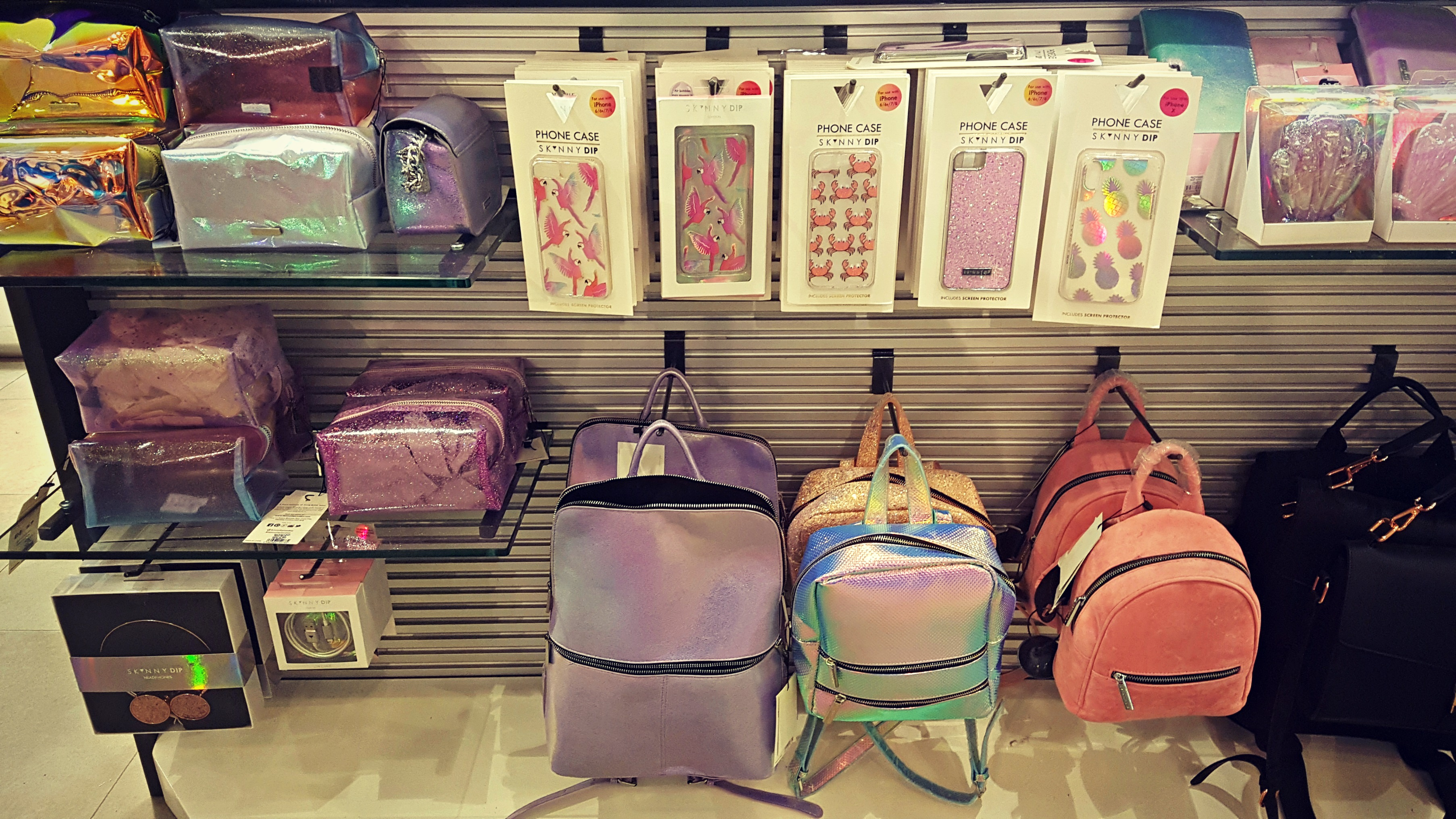 a range of skinny dip make up bags, phone cases and backpacks at a till point in an outfit store