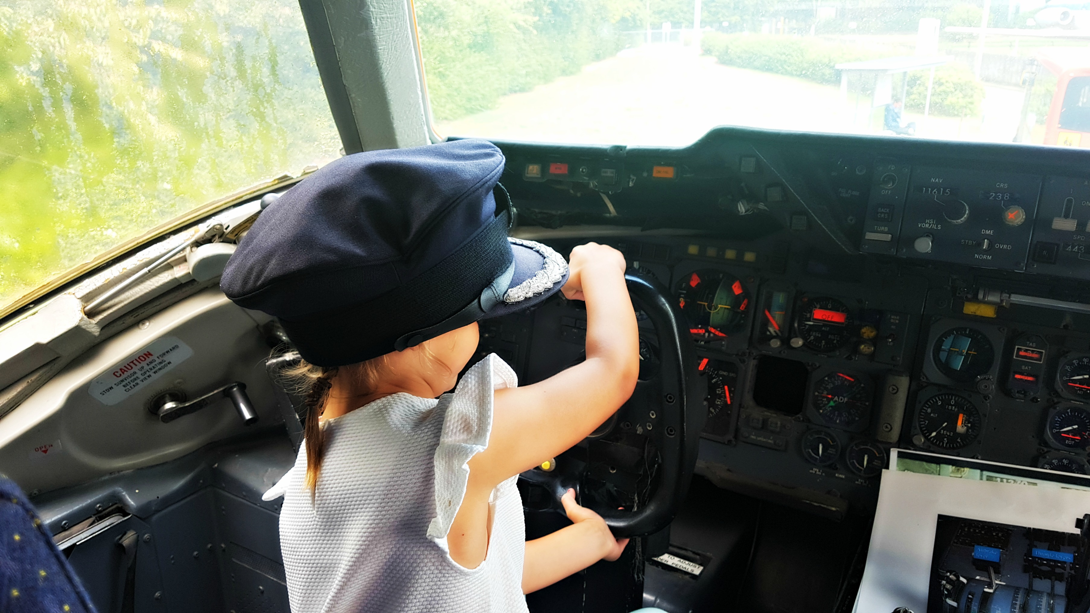 young girl with a pilot cap on sitting in a cockpit