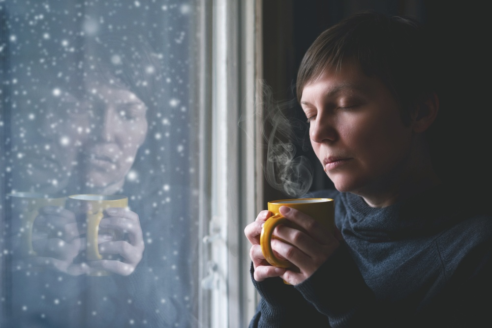 a woman with her eyes closed leaning against a window with a hot drink in a mug in her hands