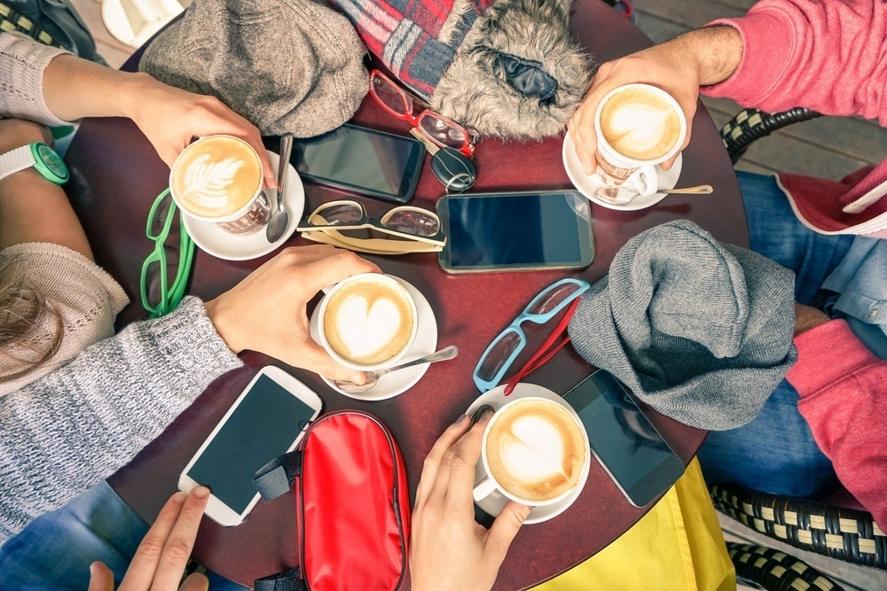 multiple hands holding cups of coffee over a table with sunglasses on and mobile phones