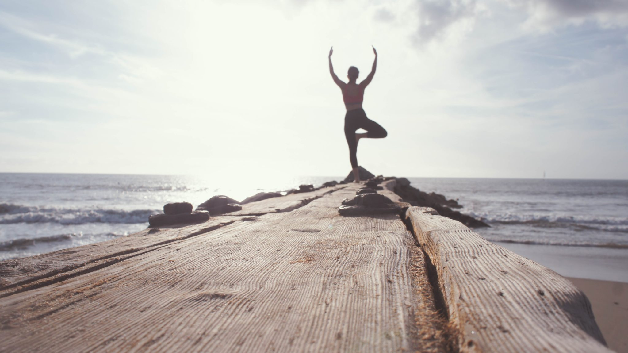 a woman in a yoga pose standing at the end of a wooden pier surrounded by water