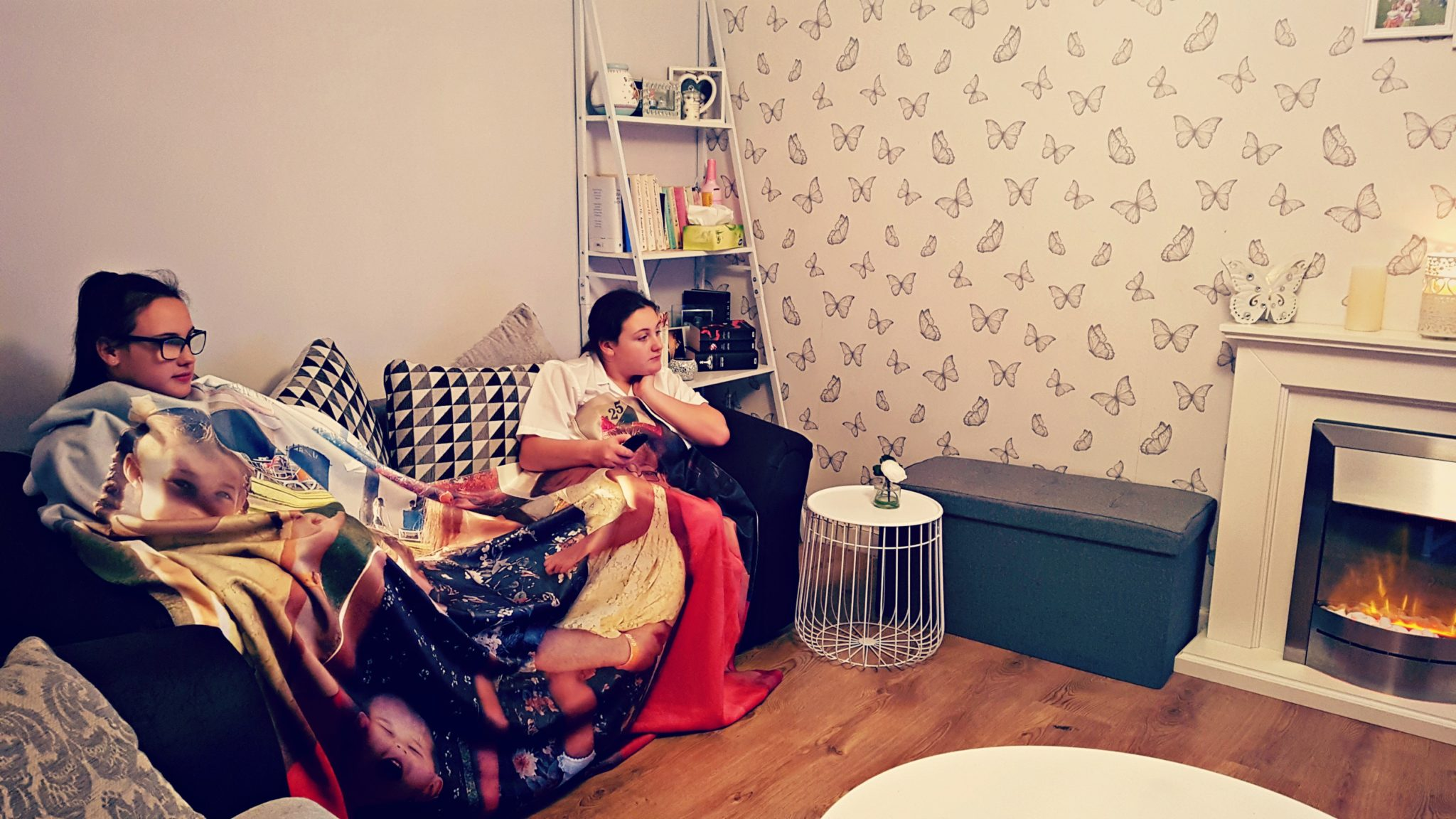 2 girls sitting on s sofa under s photo blanket in a room with white and grey accessories and white fireplace