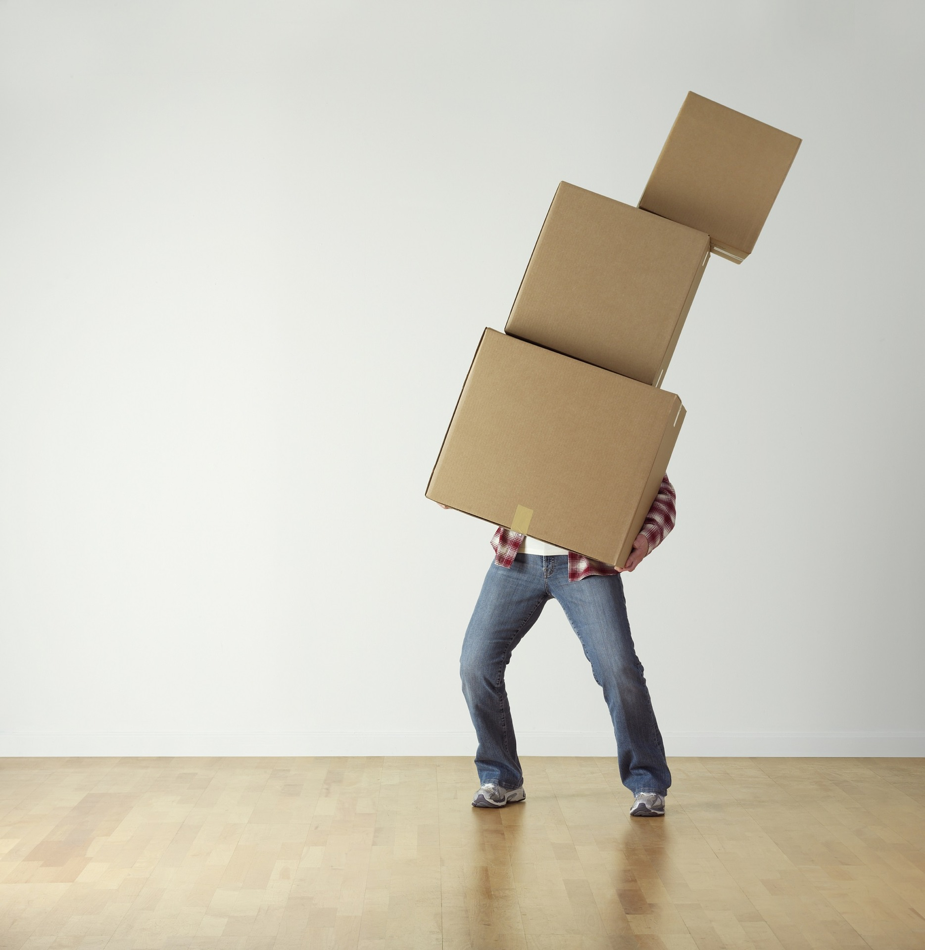 a man in an empty room carry 3 cardboard boxes