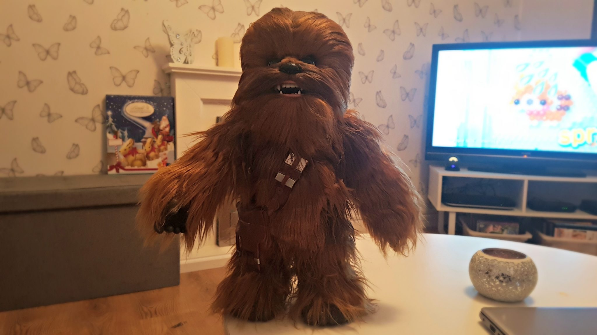 image of co-pilot chewie standing on a white table with a tv in the background
