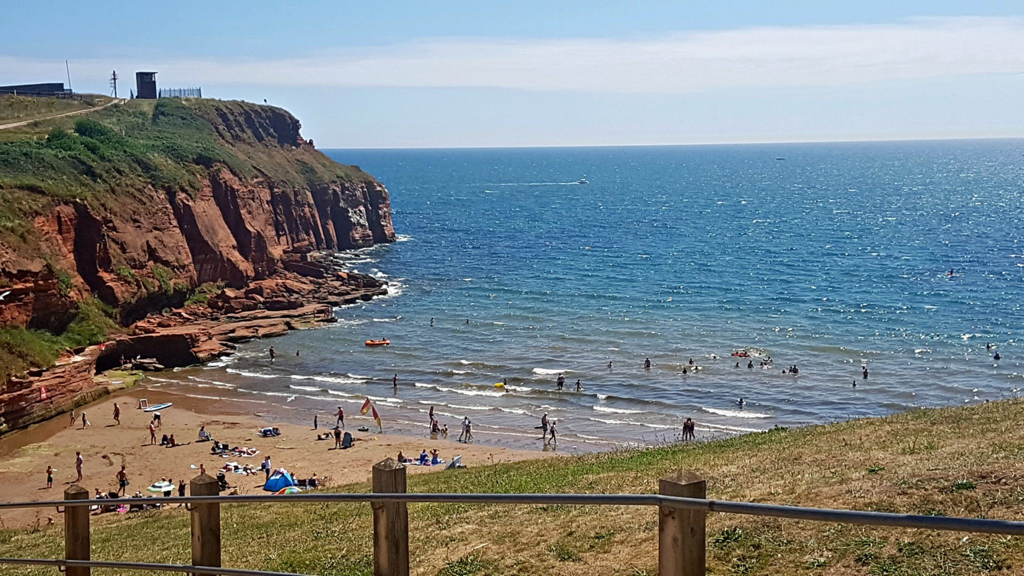 a busy beach surrounded by cliffs
