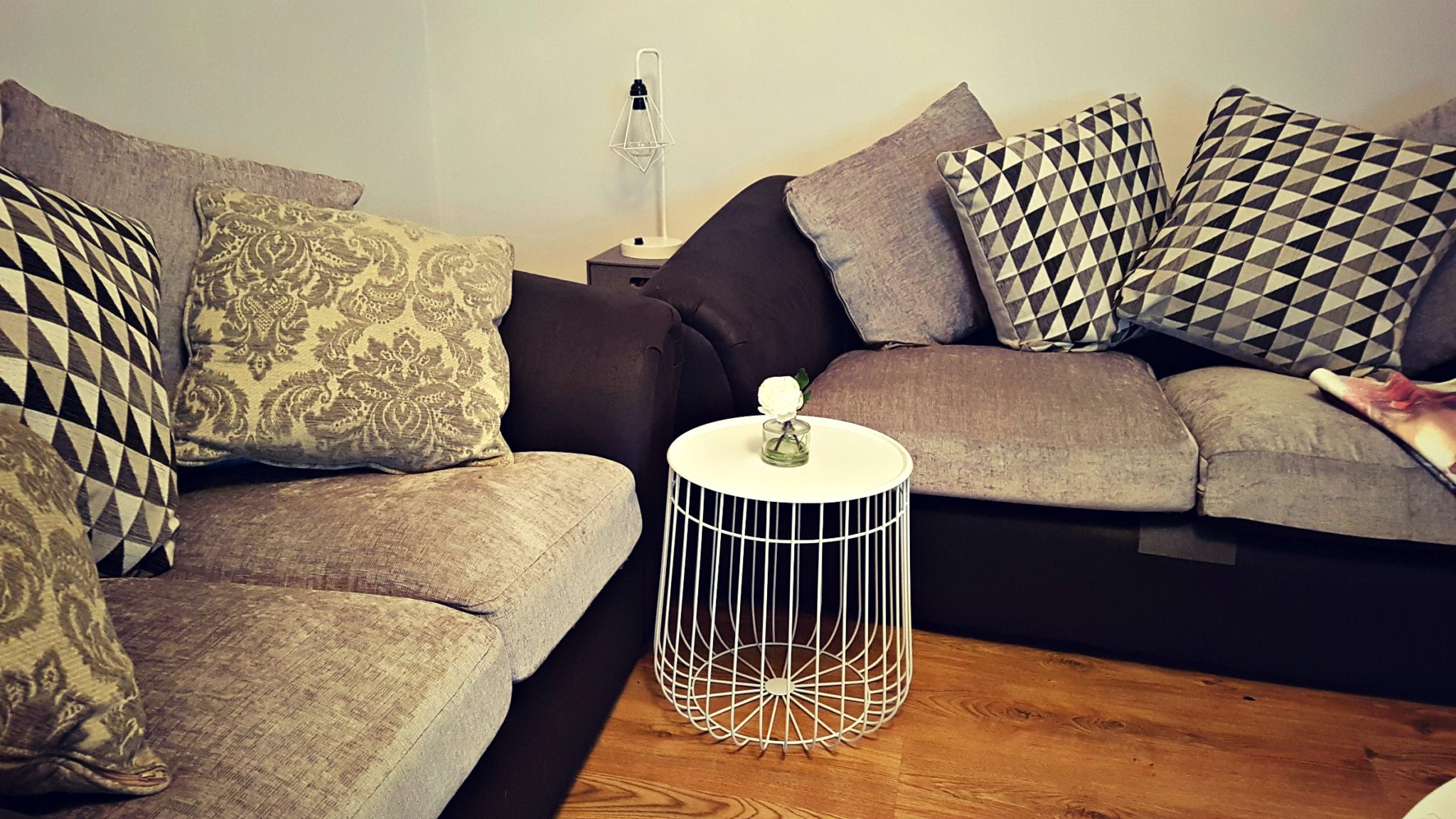 a round white side table in the corner of two grey sofas