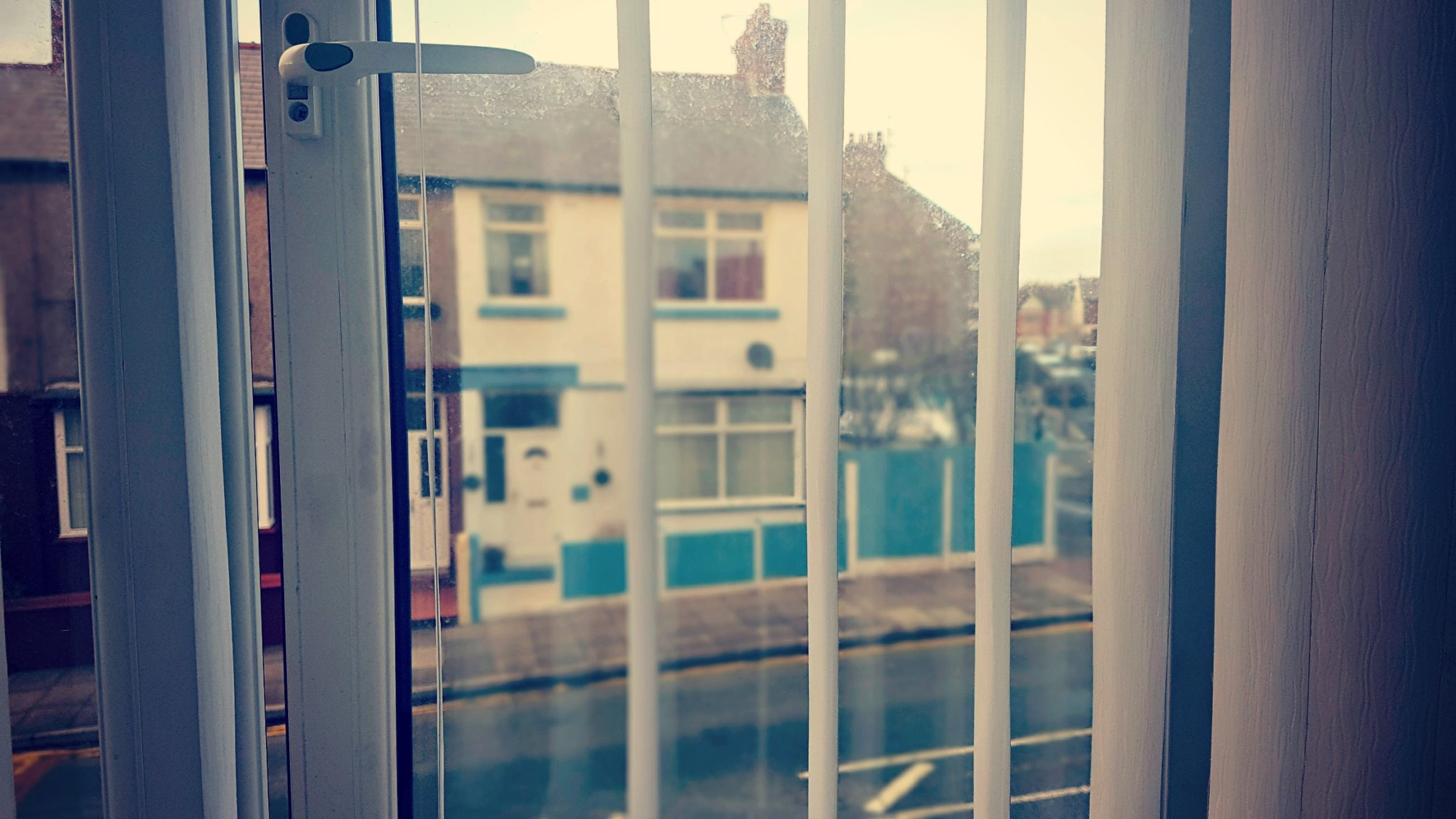 a view through an open double glazed window with blind slats open