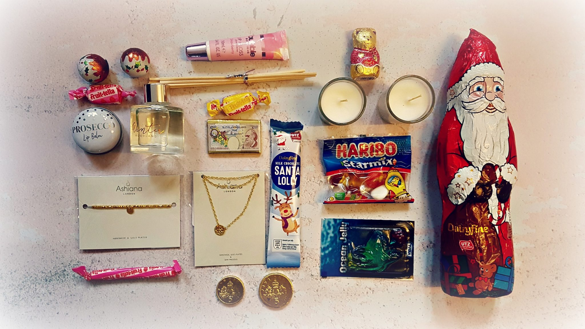 selection of christmas chocolates and sweets with a bracelet, necklace, lip balm and candle related products all arranged in flatlay
