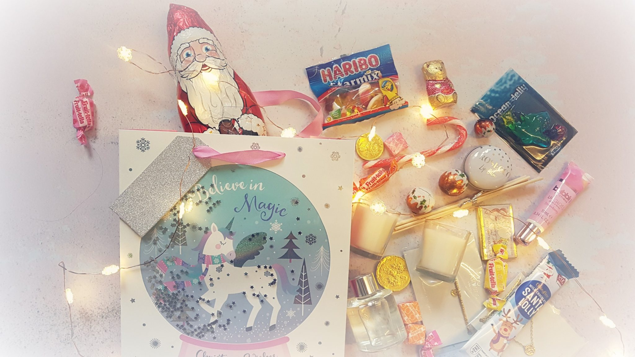 a messy flatlay with a christmas unicorn gift bag surround by christmas novelty chocolates and small gifts and led string lights