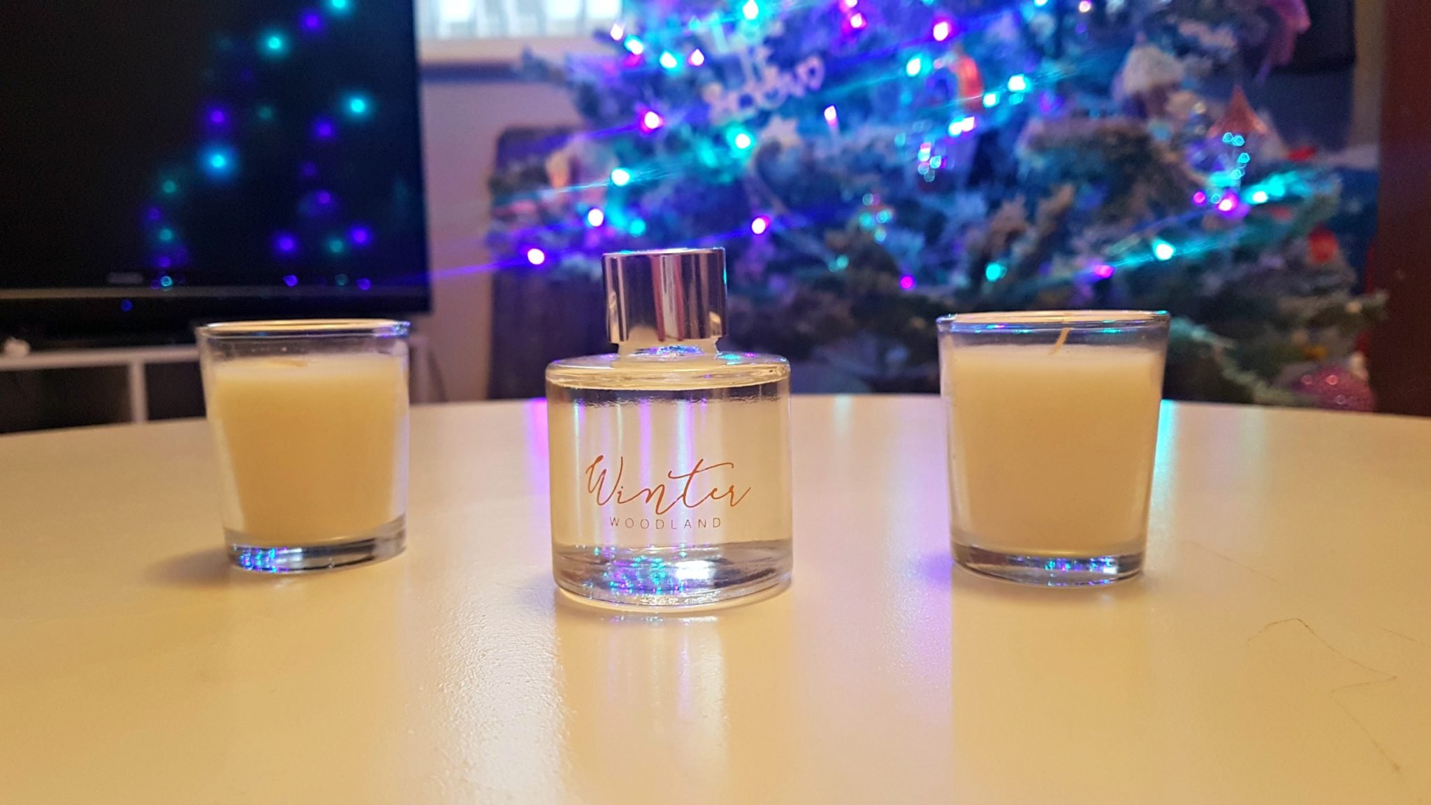 a close up of a small reed diffuser bottle with white candles either side on a white table with a christmas tree blurred in the background