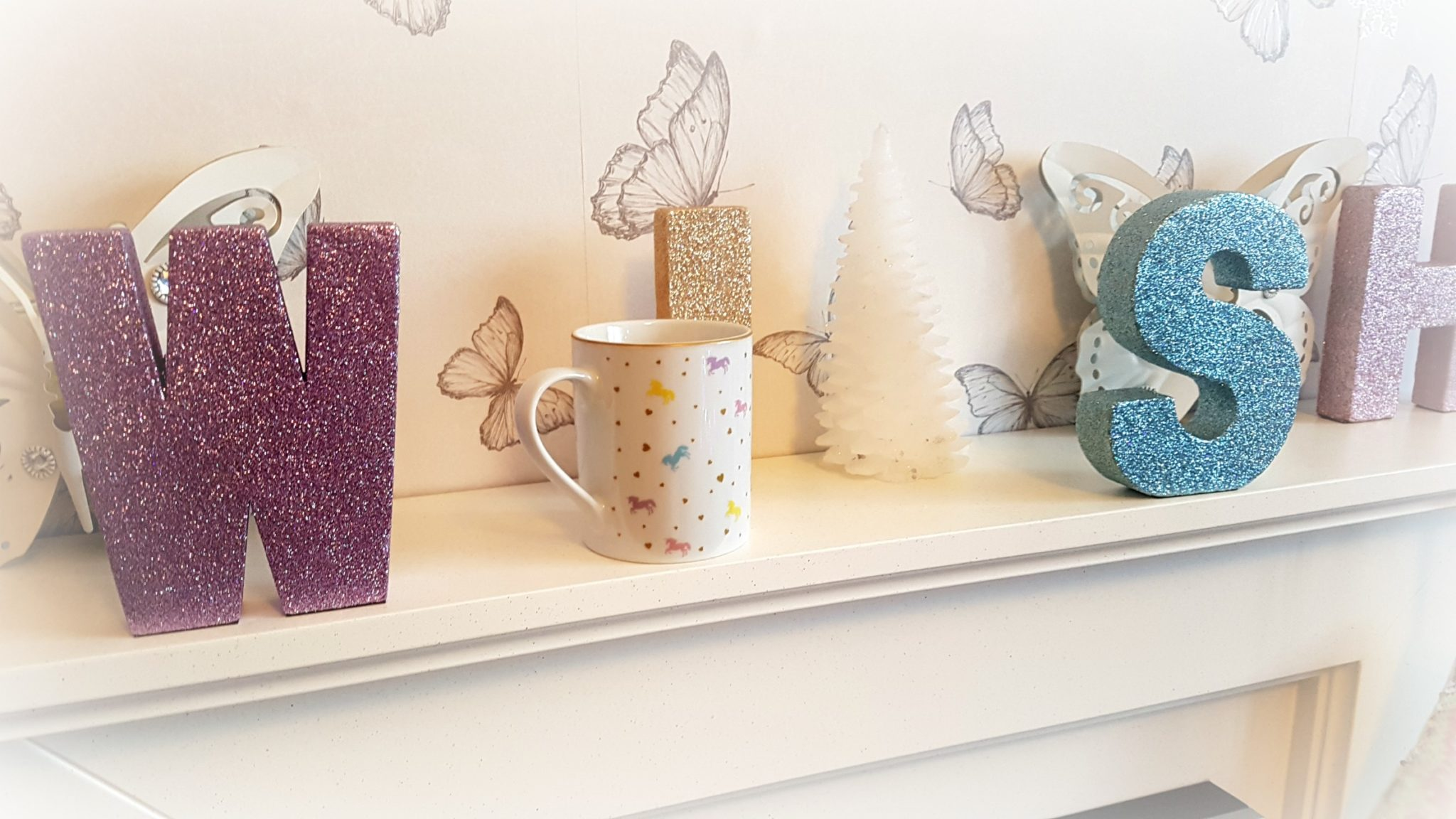 a whitel mantlepiece with pastel coloured letters spelling wish with a white candle christmas tree and a unicorn designed mug