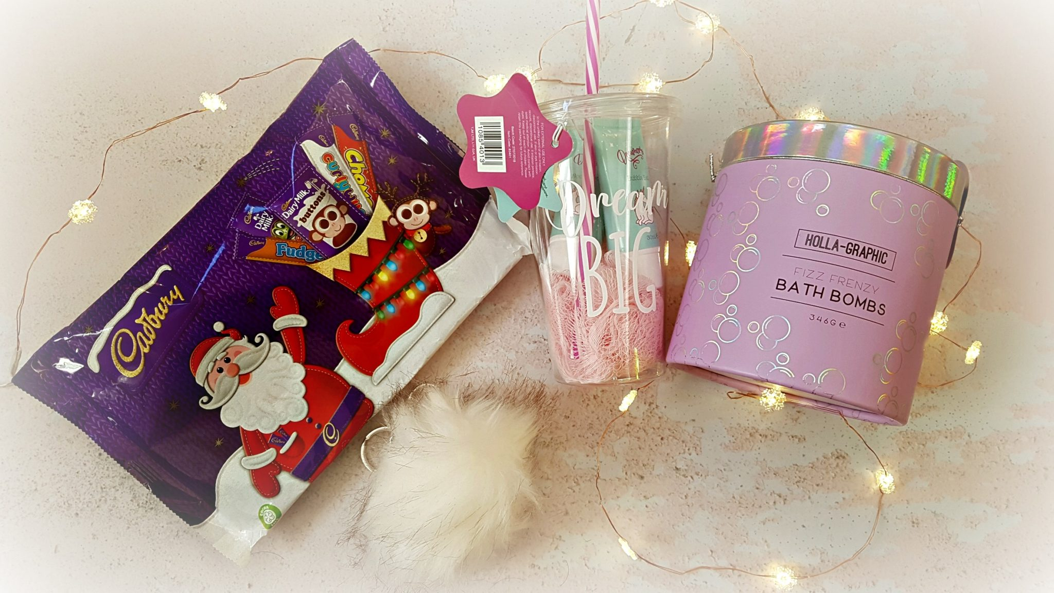 a flatlay selection of childrens gifts from home bargains including a small chocolate selection box a tub of bath bombs and a clear cup with straw filled with unicorn branded bath products