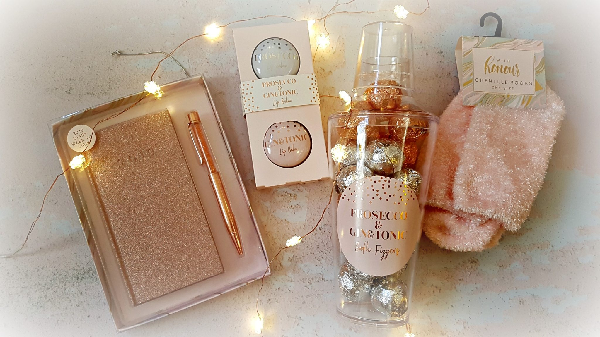 a flatlay of home bargains christmas gifts including a rose gold diary and pen set, lip balm tins, fluffy pink socks and a tub of prosecco and gin bath fizzers