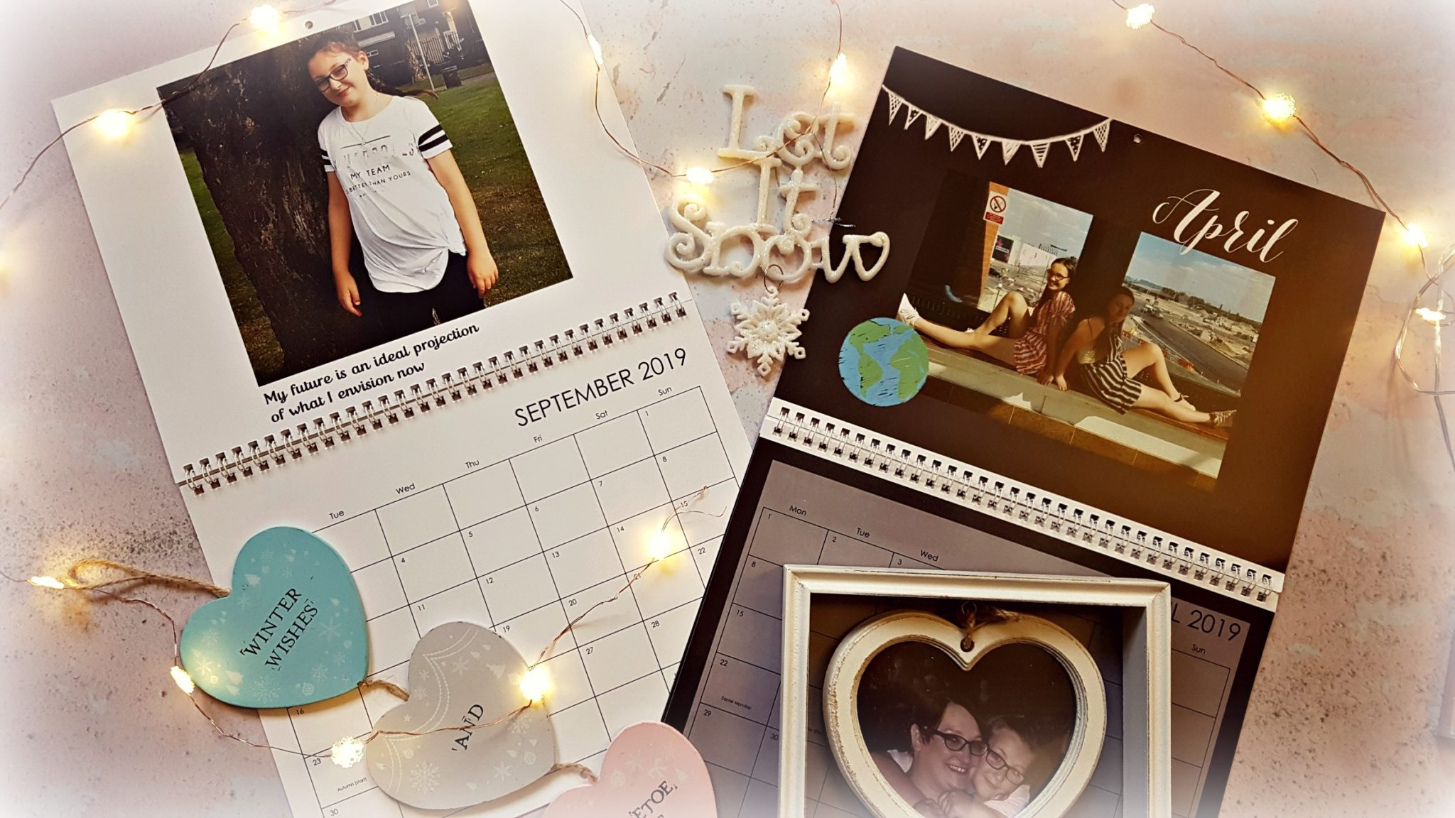 two open truprint personalised calenders with wooden heart decorations, a wooden heart picture frame and snowflake fairy lights