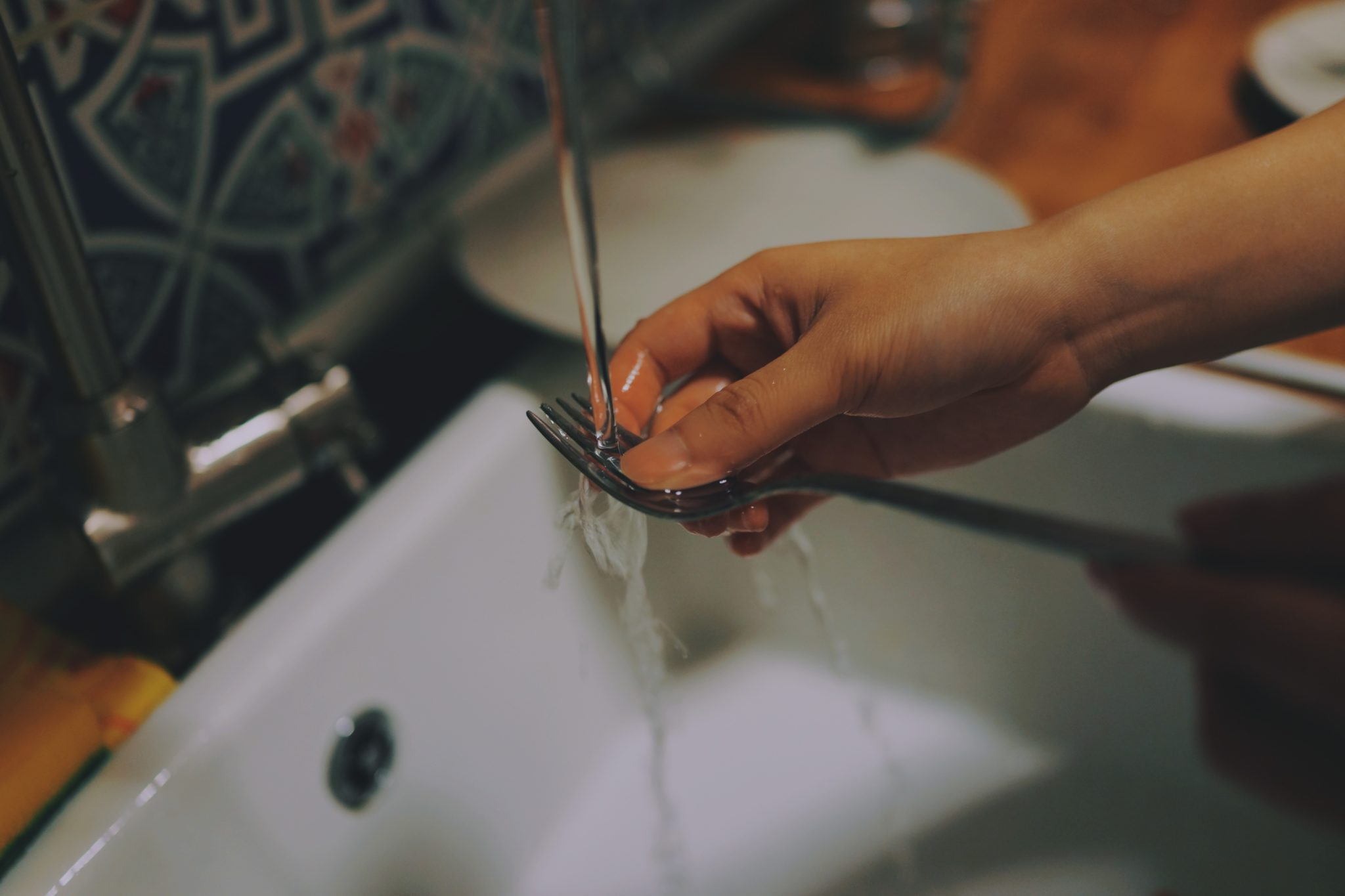 a fork being washed in running water