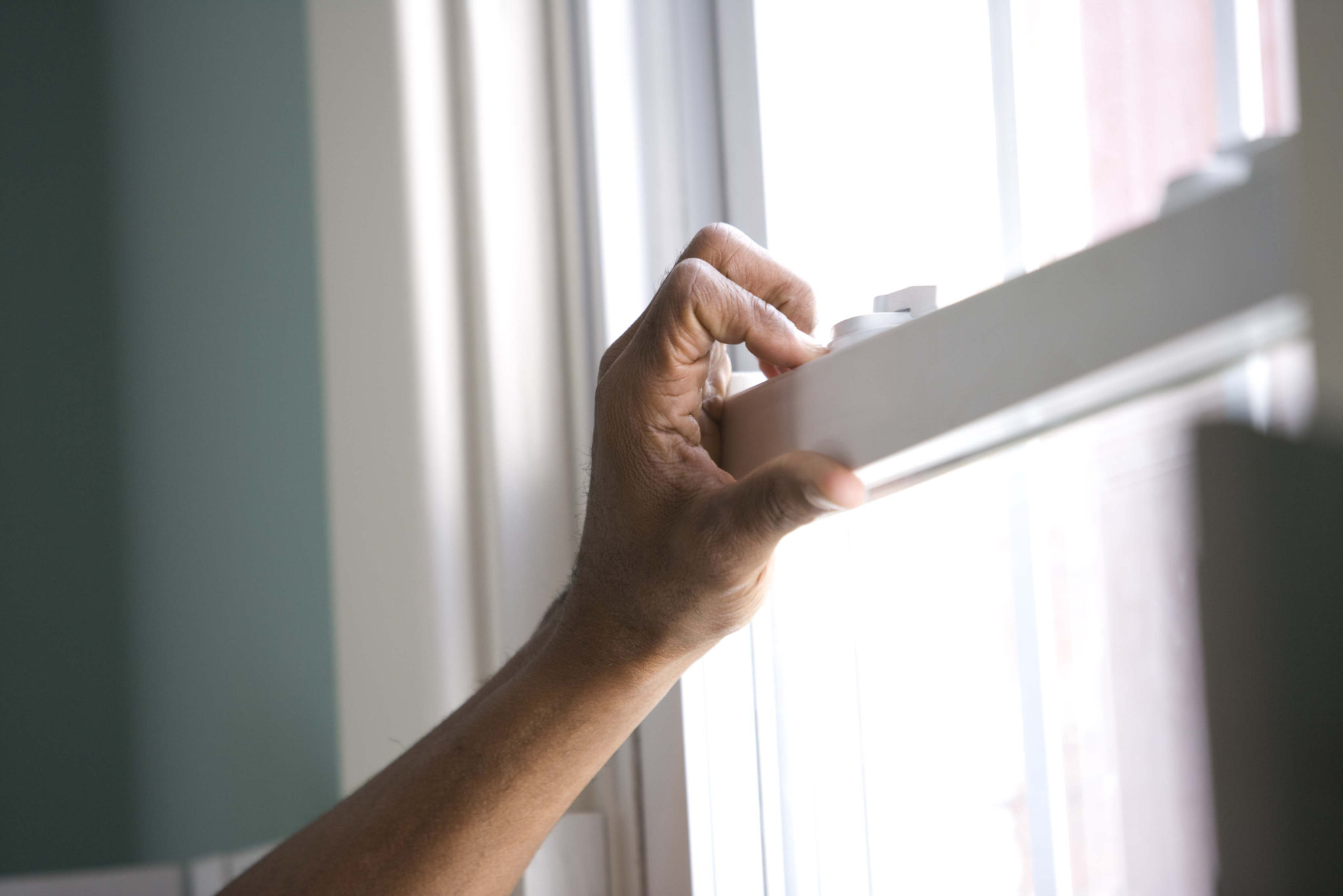 a hand opening a a sash window