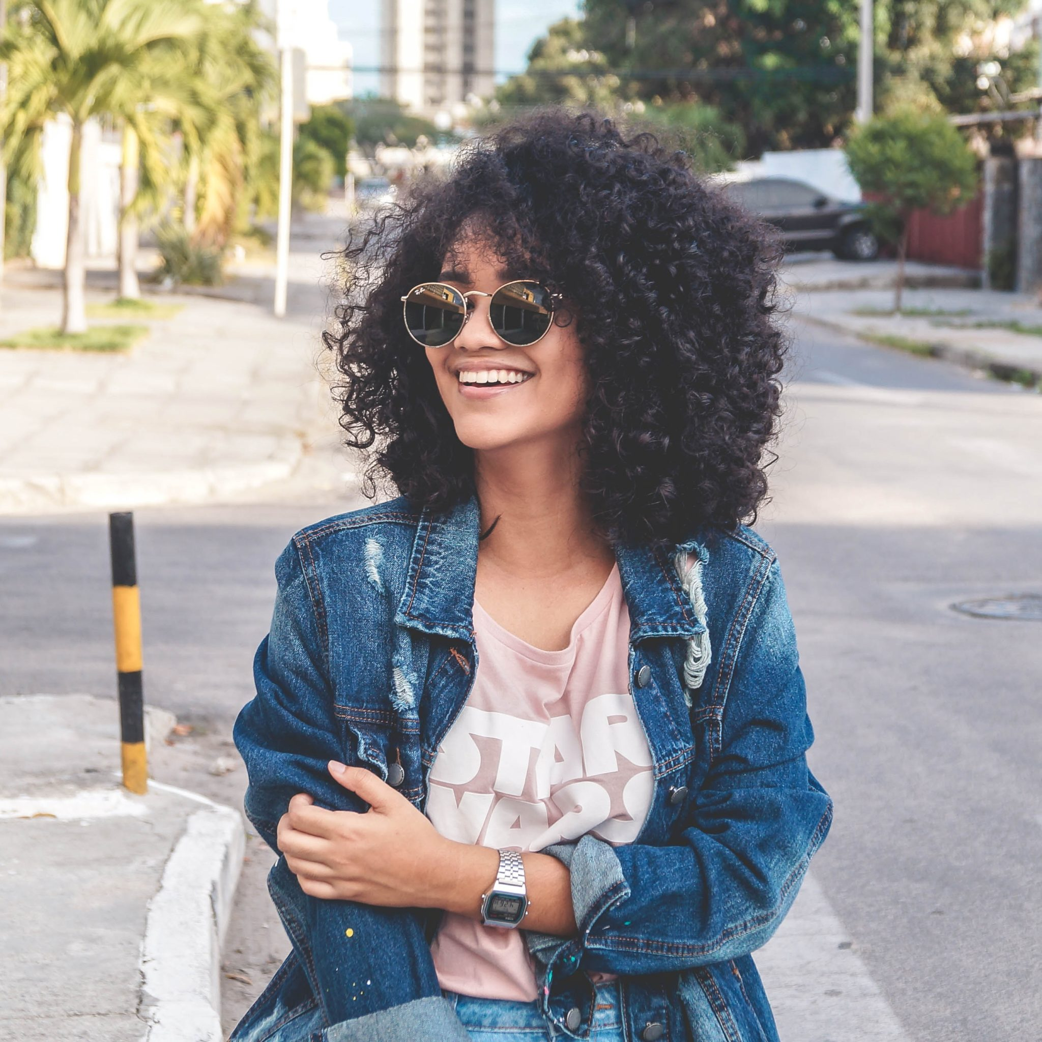girl with curly hair wearing sunglasses standing in road with a denim jacket on, arms folded in front of her with a star wars tshirt showing under the jacket