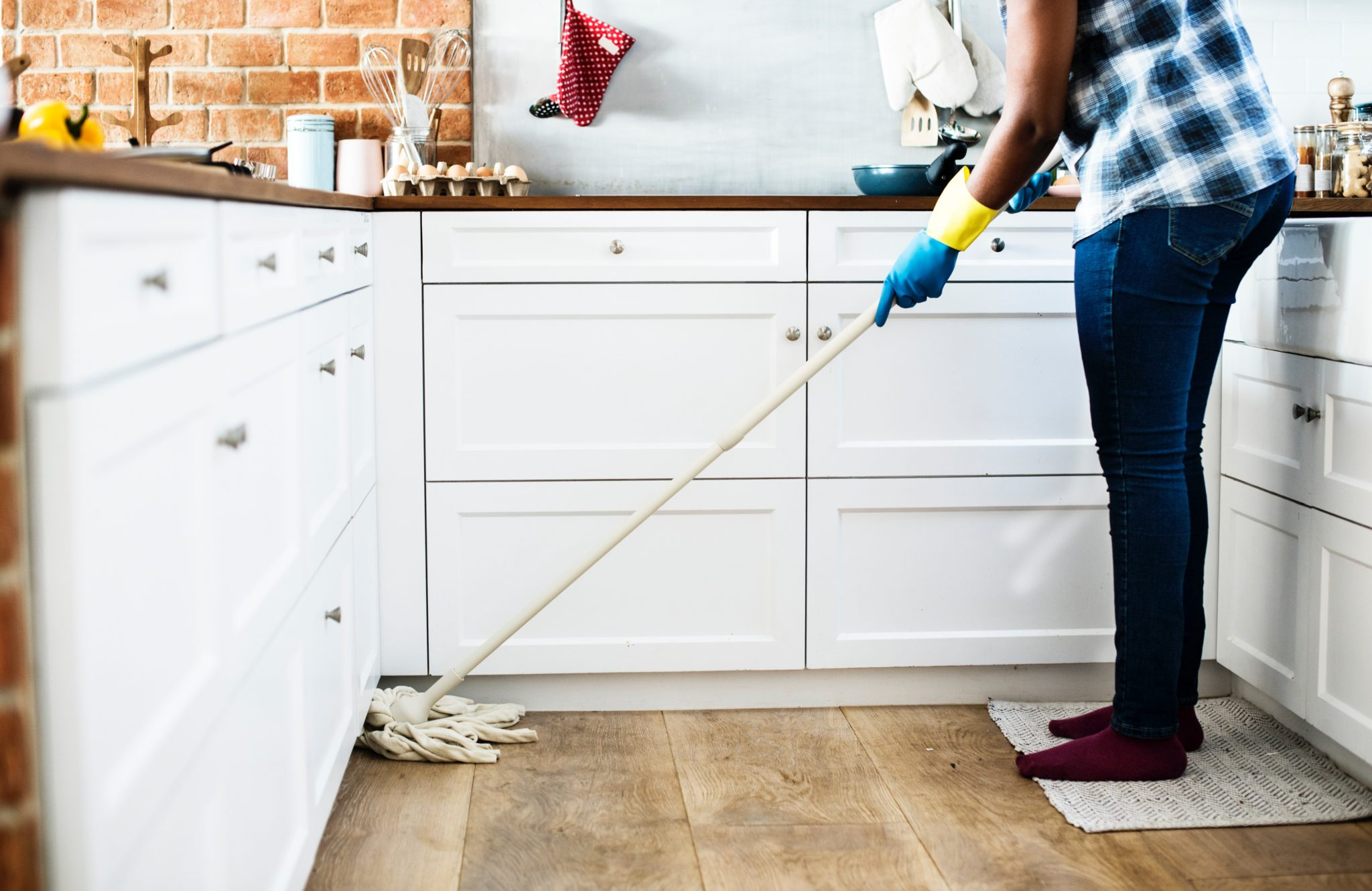 a person using a mop to clean a wooden floor with white units in the background