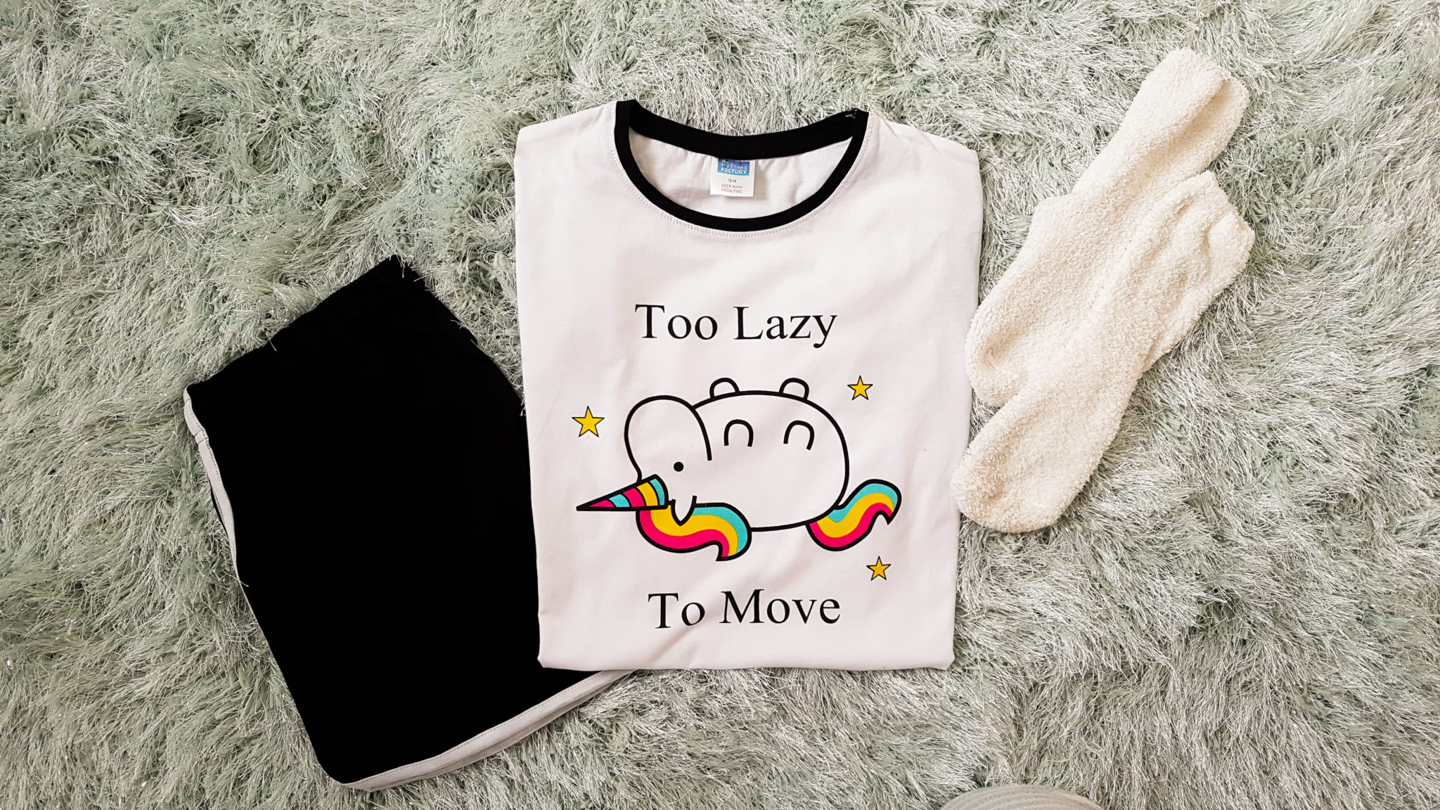 flatlay of a white pyjama top with a unicorn on and quote saying too lazy to move with black shorts and white socks on a duck egg rug