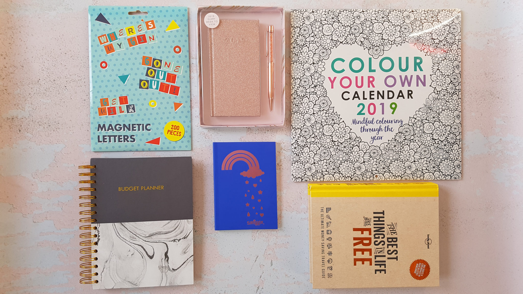 flatlay of items including a calendar, notbooks, budget planner and diary