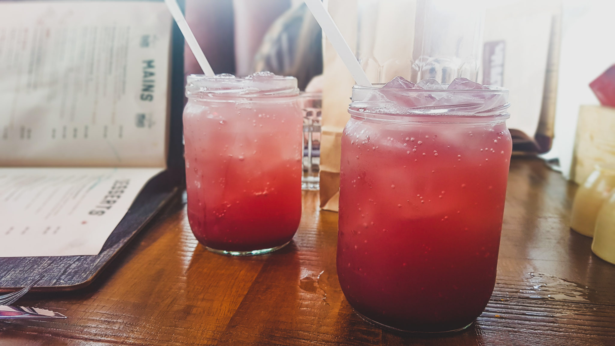 two glasses of cherry cream soda on a table with a menu open in the background