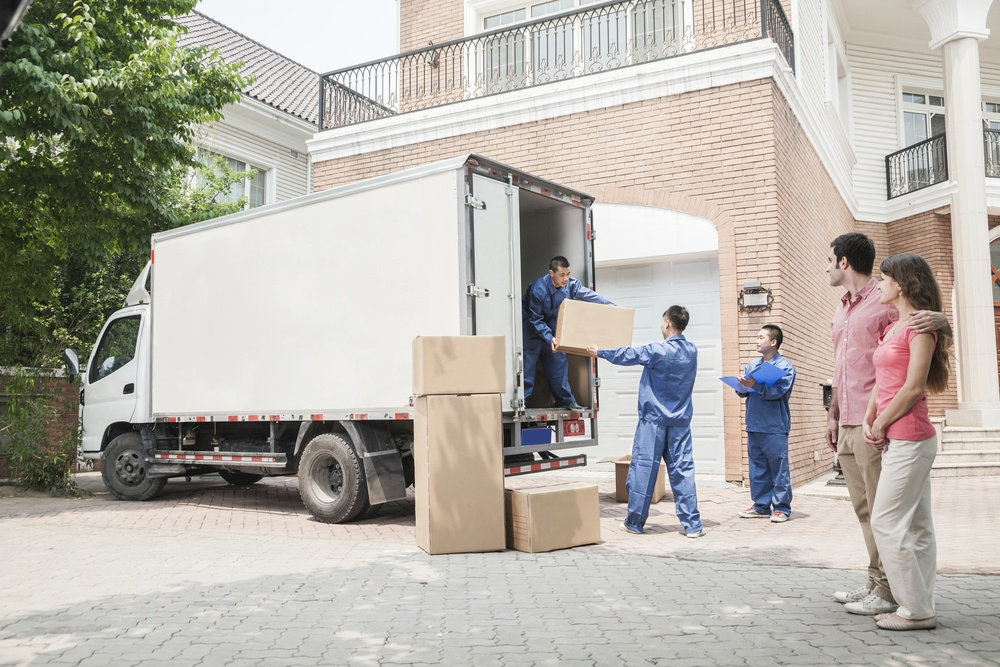 couple standing watching removal men take boxes off a white lorry
